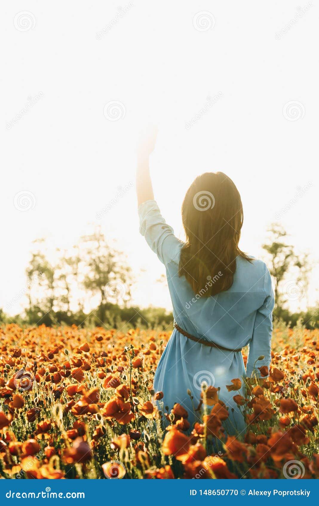 Mulher que anda no campo da papoila no dia de verão ensolarado