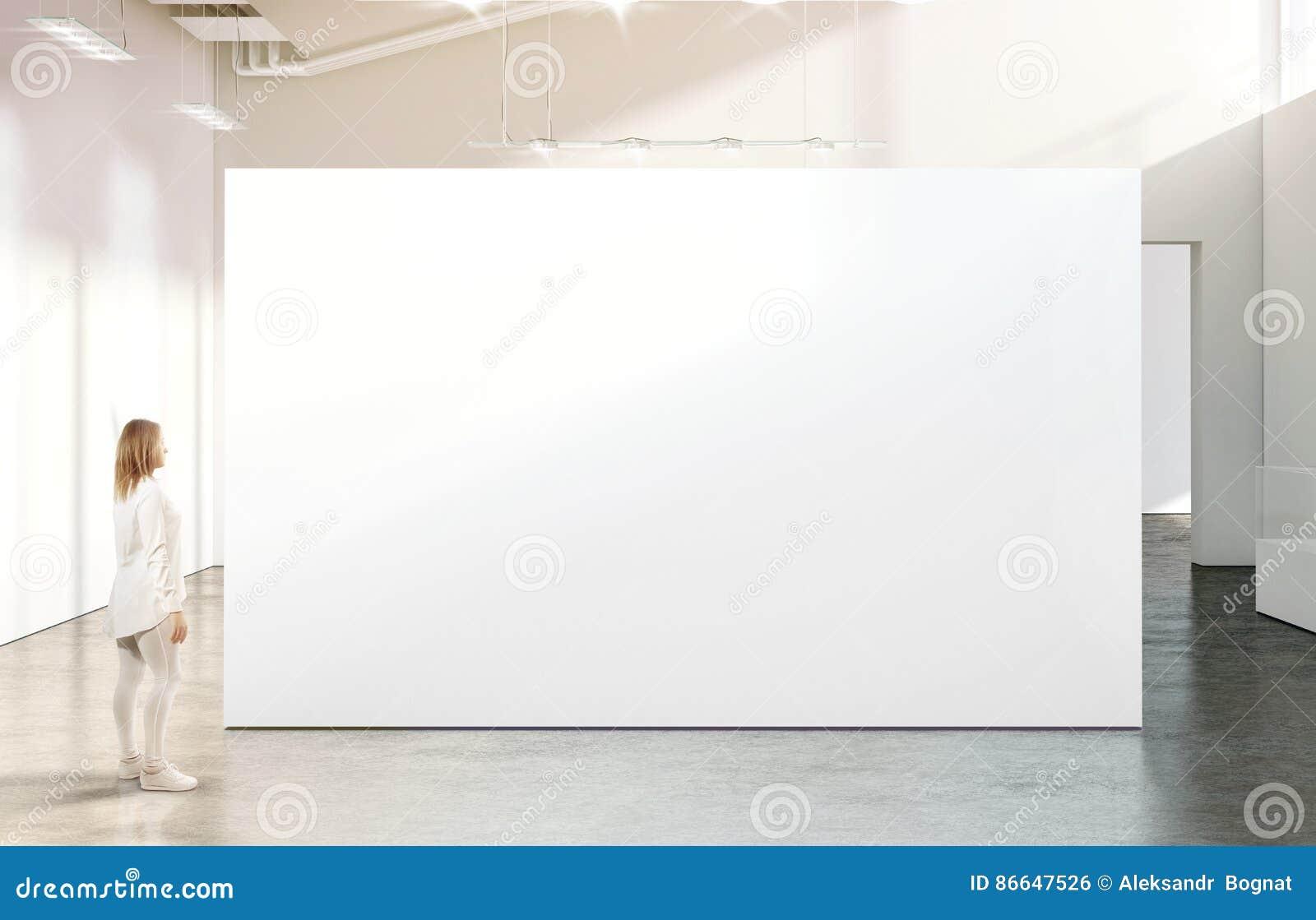 Mulher que anda perto do modelo branco vazio da parede na galeria moderna