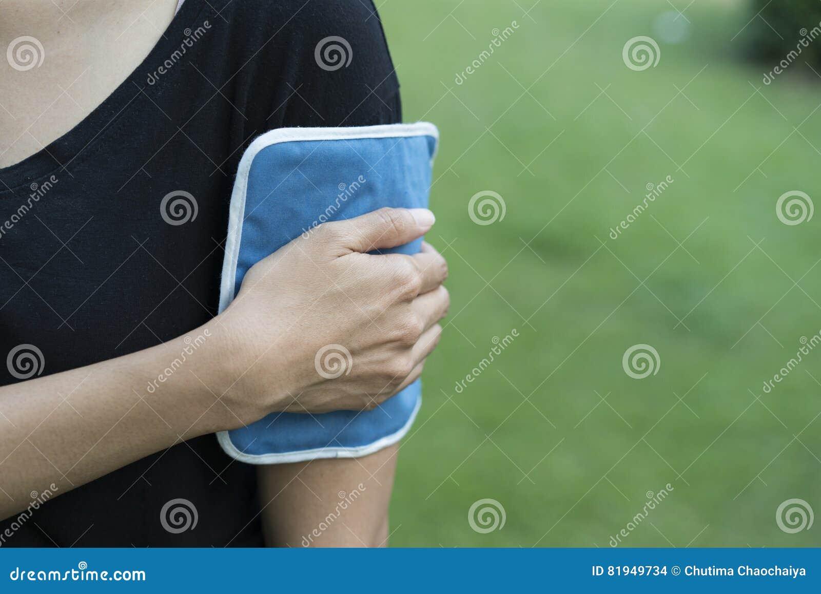 Bolsa De Gelo Ombro : Mulher que aplica a bolsa de gelo em seu bra?o foto