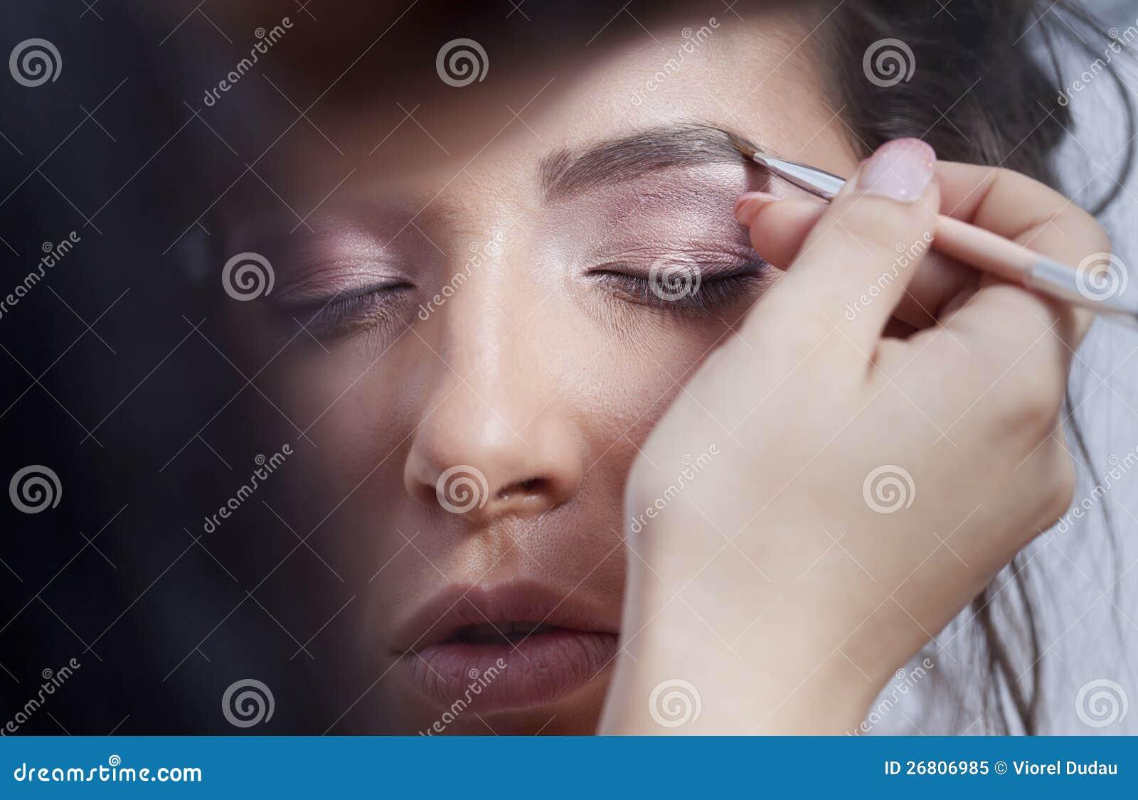Mulher que aplica a composição do olho