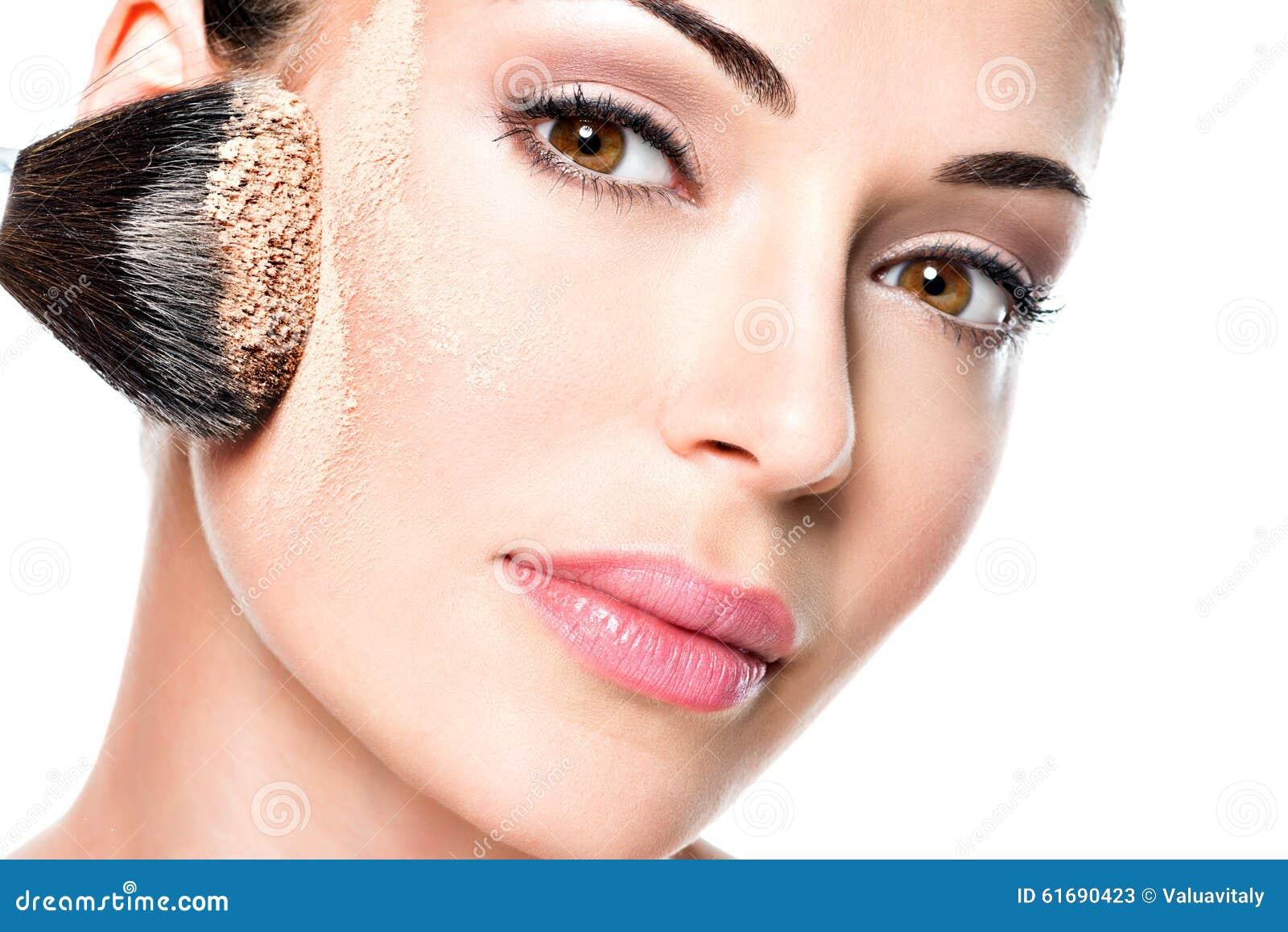 Mulher que aplica a fundação tonal cosmética seca na cara
