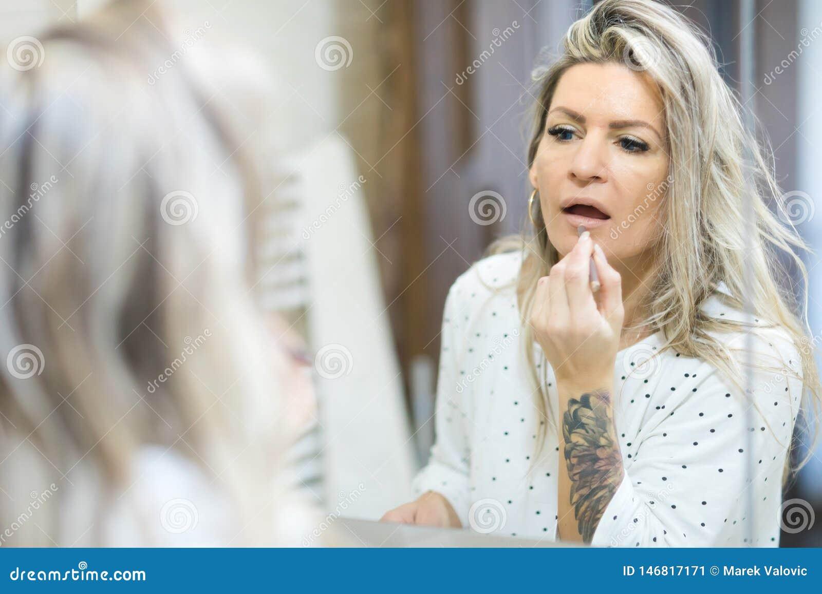 A mulher que aplica a manh? comp?e no espelho do banheiro