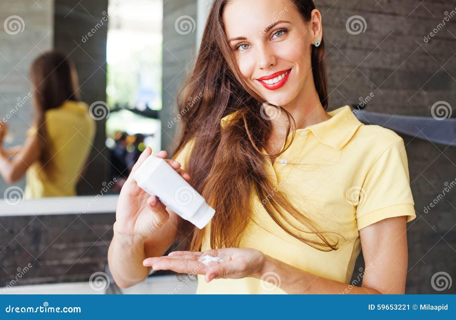 Mulher que aplica o champô seco em seu cabelo