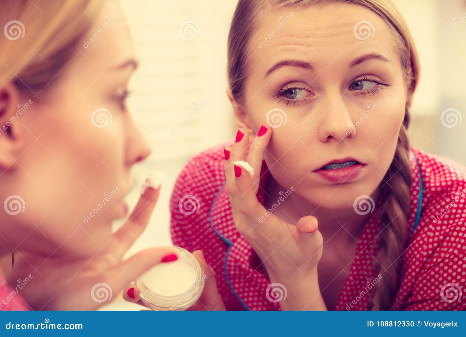 Mulher que aplica o creme de pele hidratando Skincare