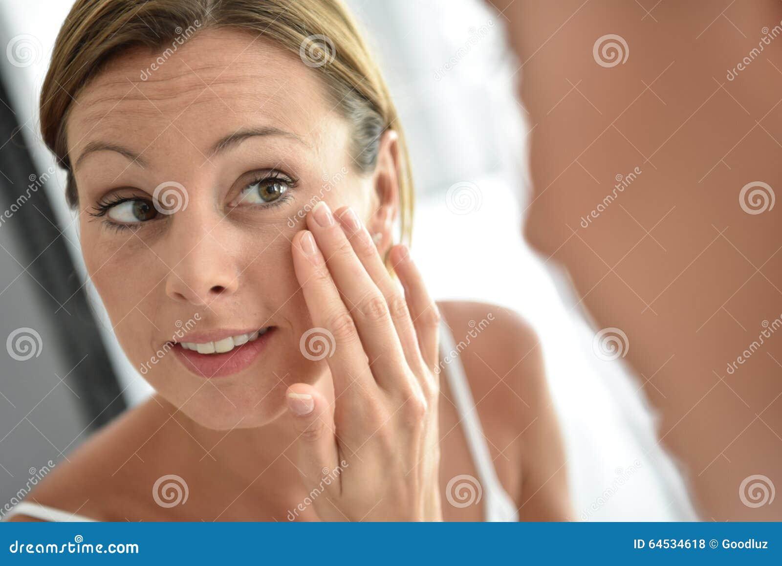 Mulher que aplica o creme diário em sua cara