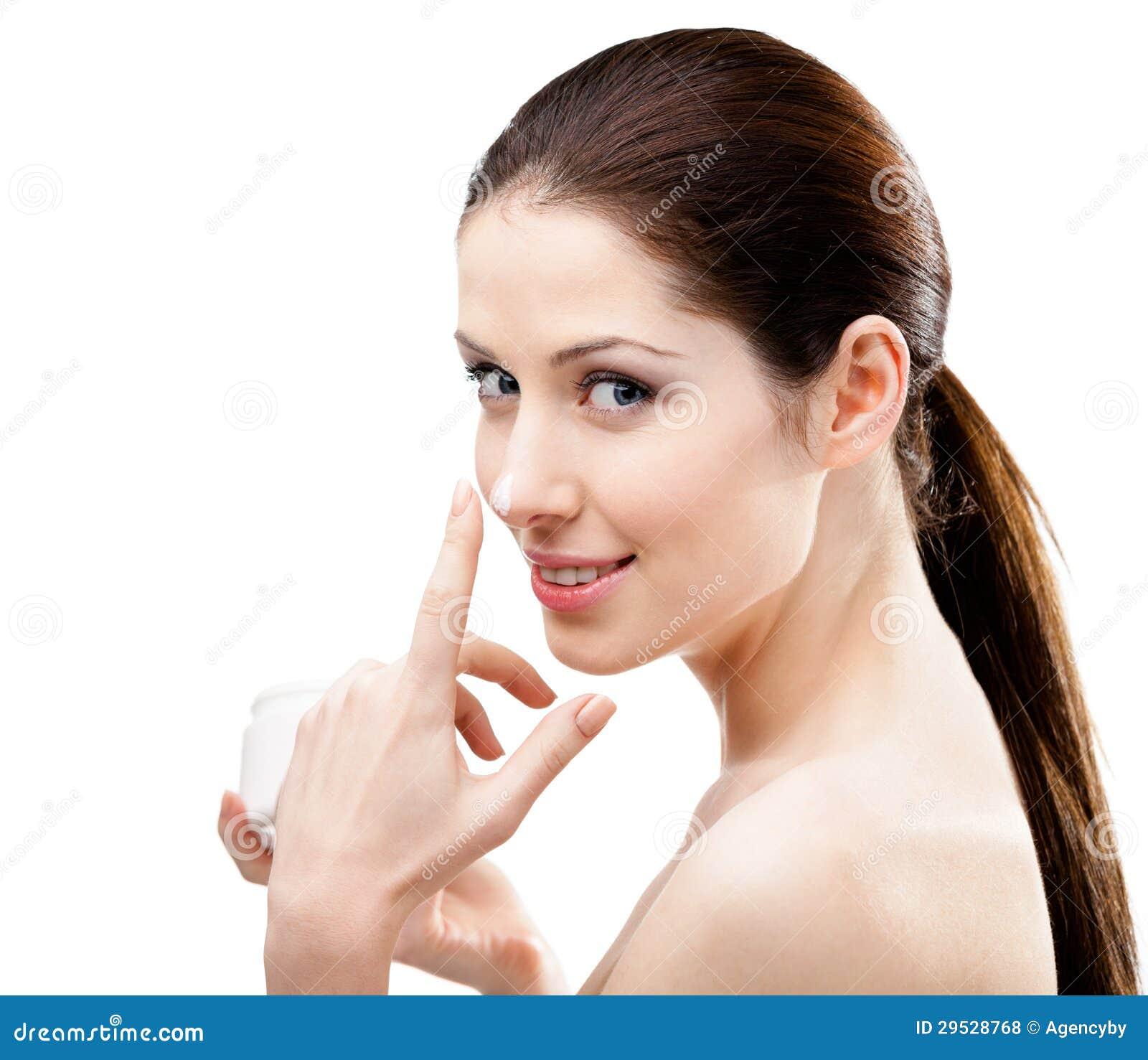 Mulher que aplica o creme em seu nariz