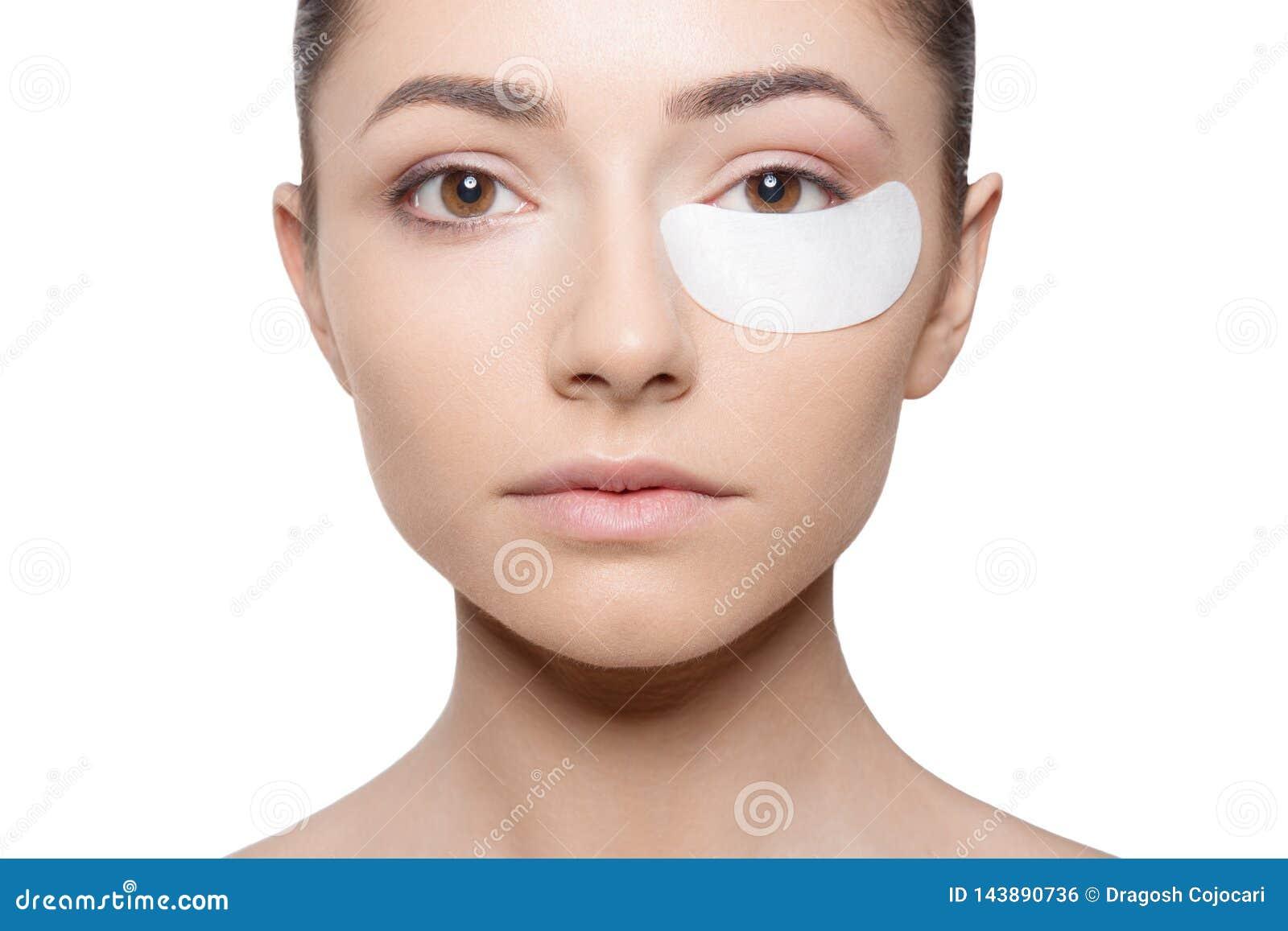 A mulher que aplica seu emplastro sob seu olho durante compõe, isolado no fundo branco Vista horizontal