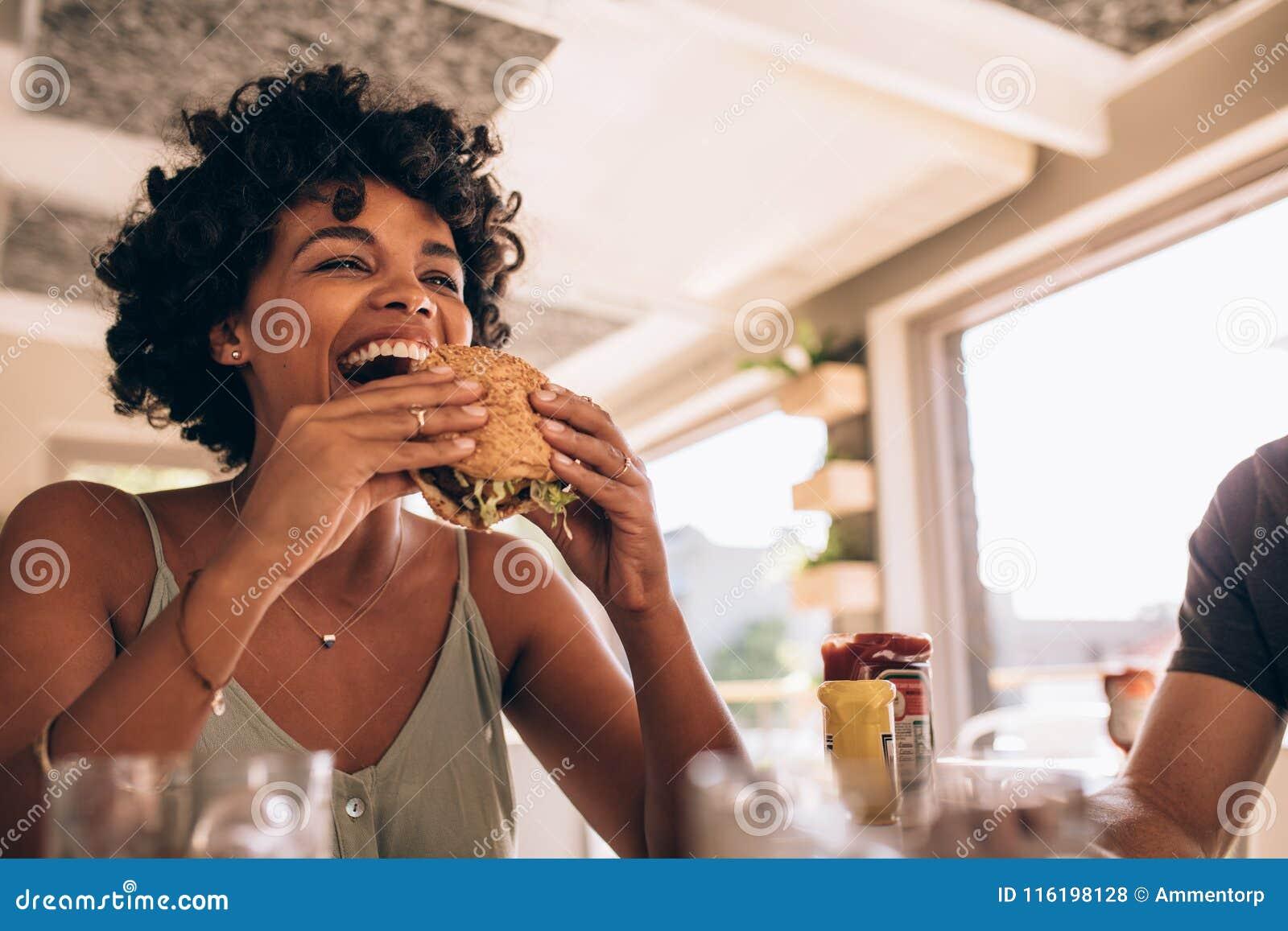 Mulher que aprecia comendo o hamburguer no restaurante