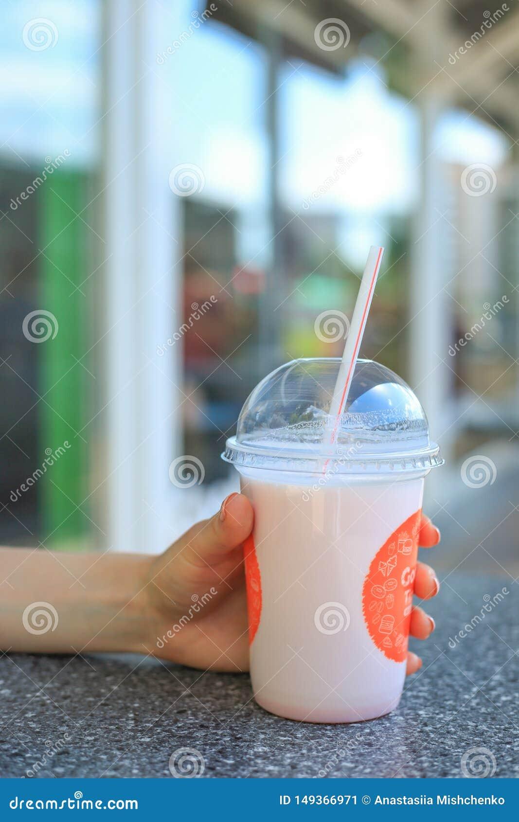 Mulher que aprecia o batido cor-de-rosa Mo?a que guarda o milk shake em um vidro com uma palha em um caf? fora no ver?o