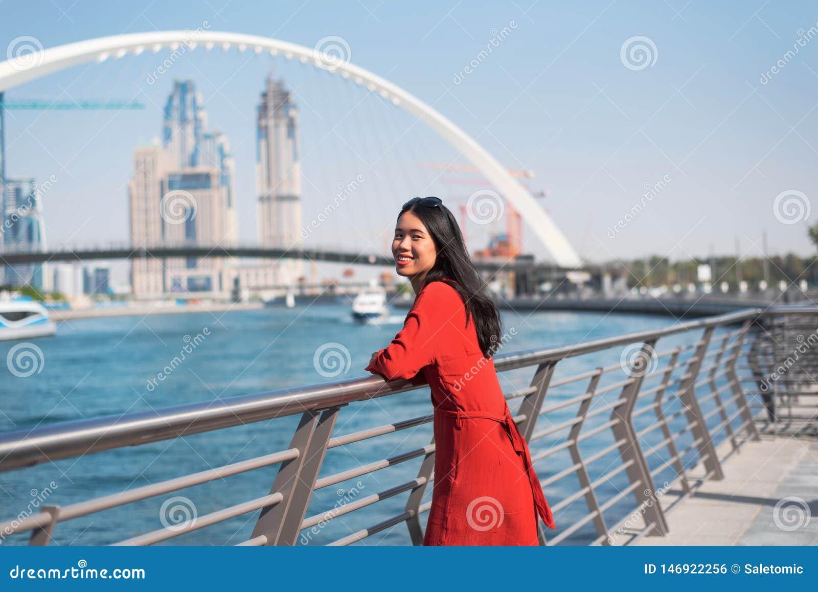 Mulher que aprecia a opinião de Dubai do canal da água