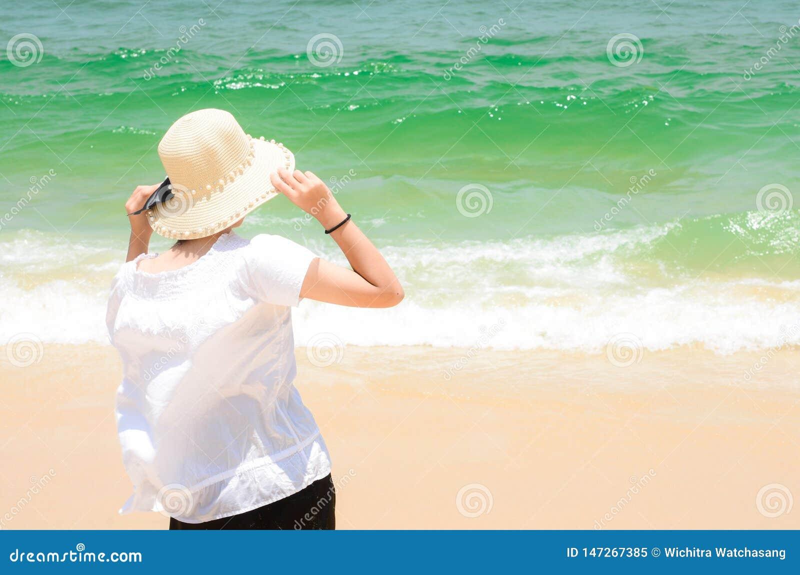 Mulher que aprecia a vista no oceano