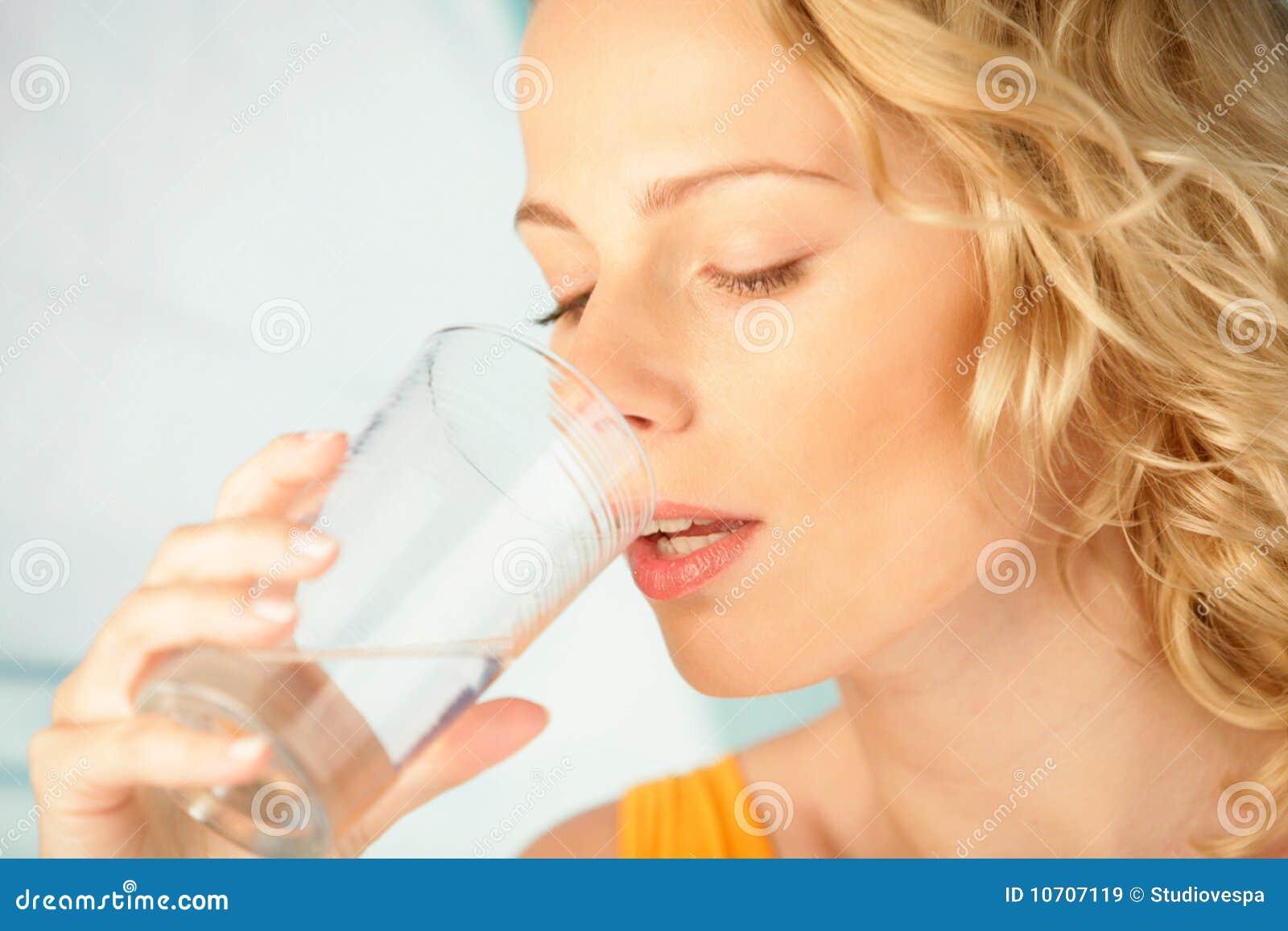 Mulher que bebe a água mineral