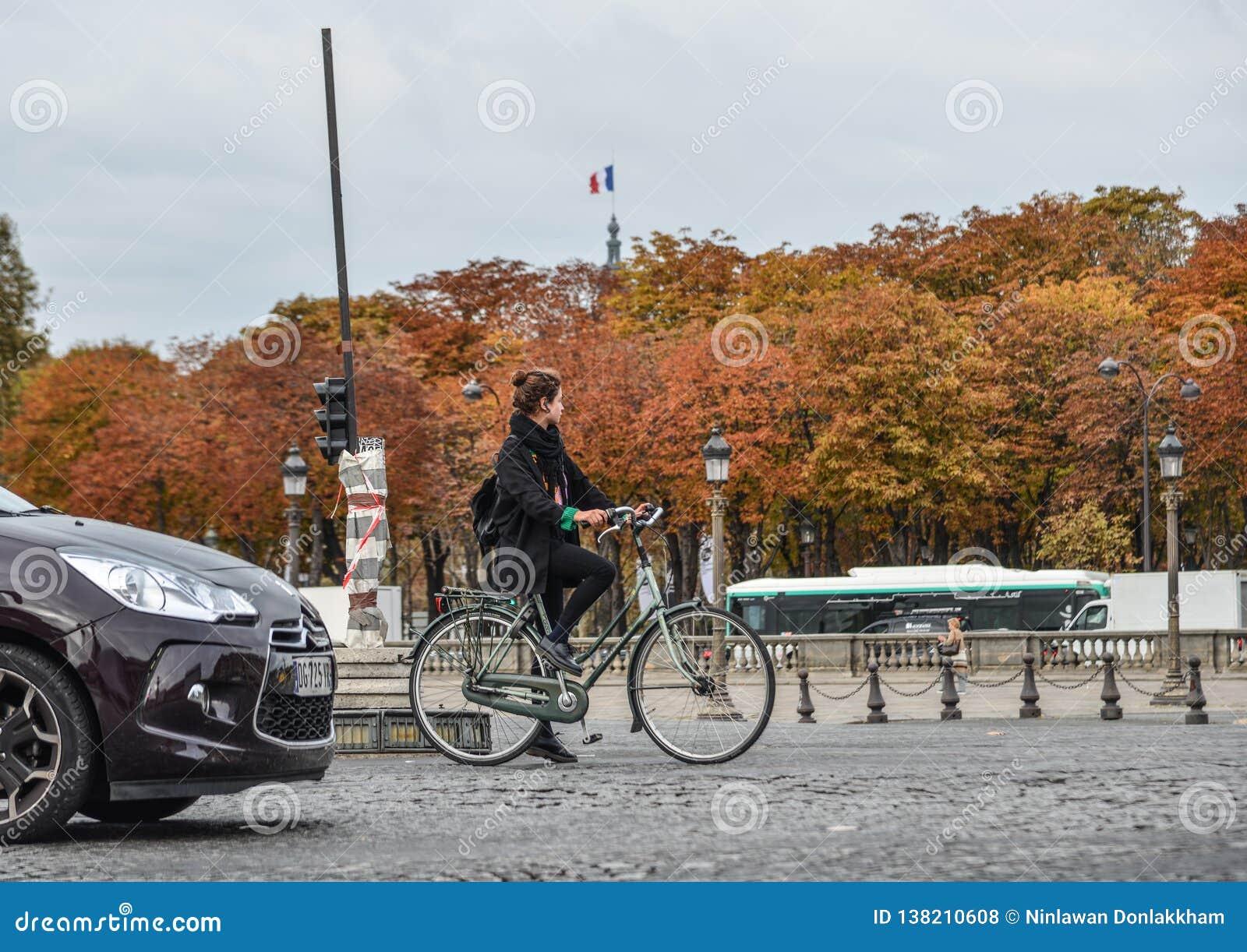 Mulher que biking na rua de Paris, França