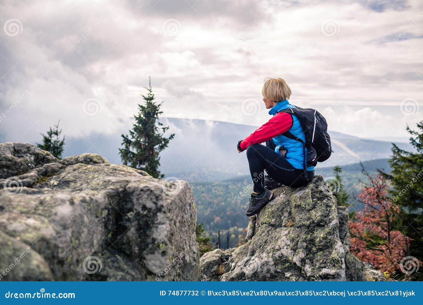 Mulher que caminha em montanhas e em madeiras do outono