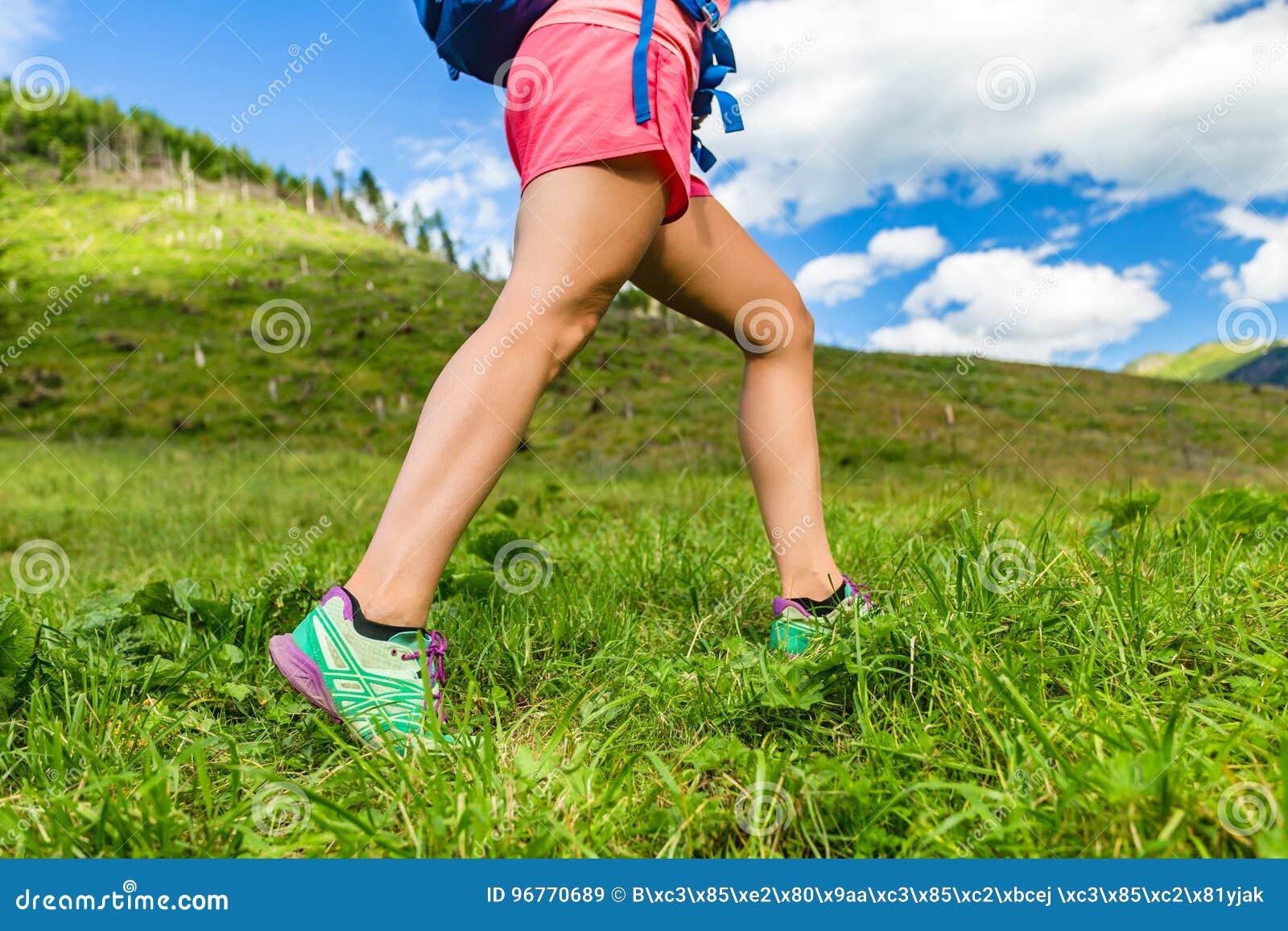 Mulher que caminha nas montanhas, na aptidão e no esporte fora
