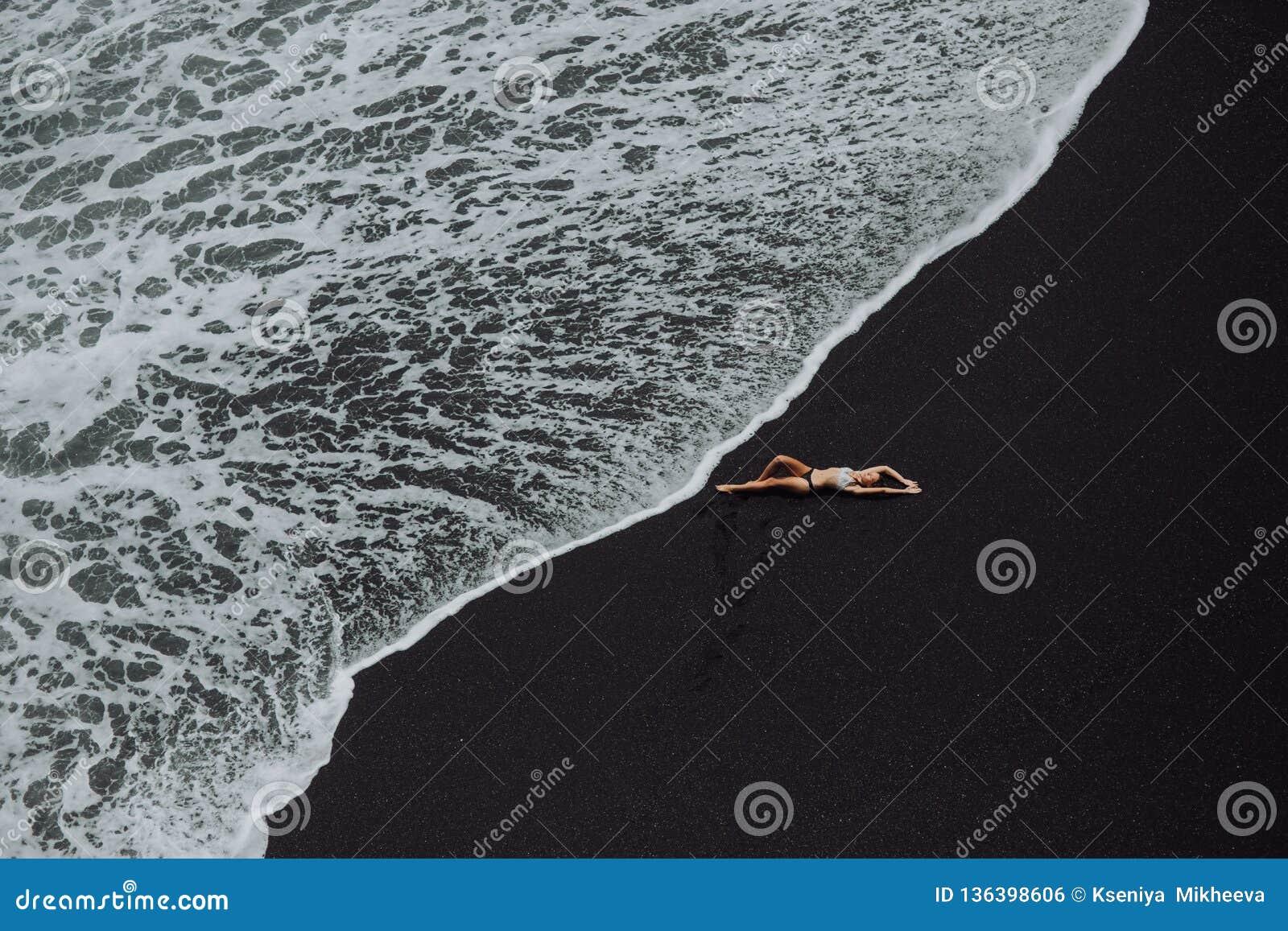 Mulher que coloca na areia tropical do preto da praia no biquini branco