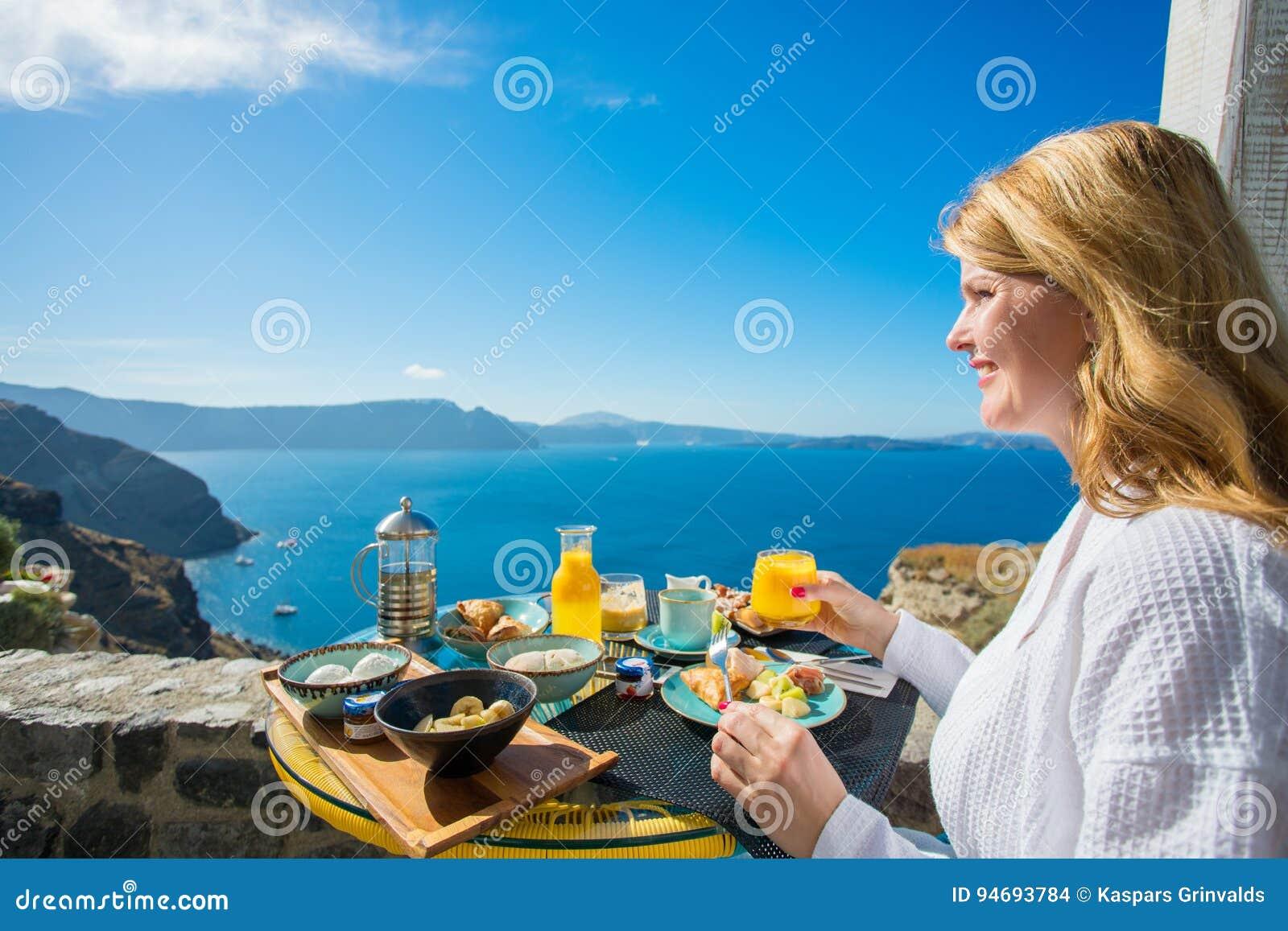 Mulher que come o café da manhã delicioso no recurso luxuoso em mediterrâneo