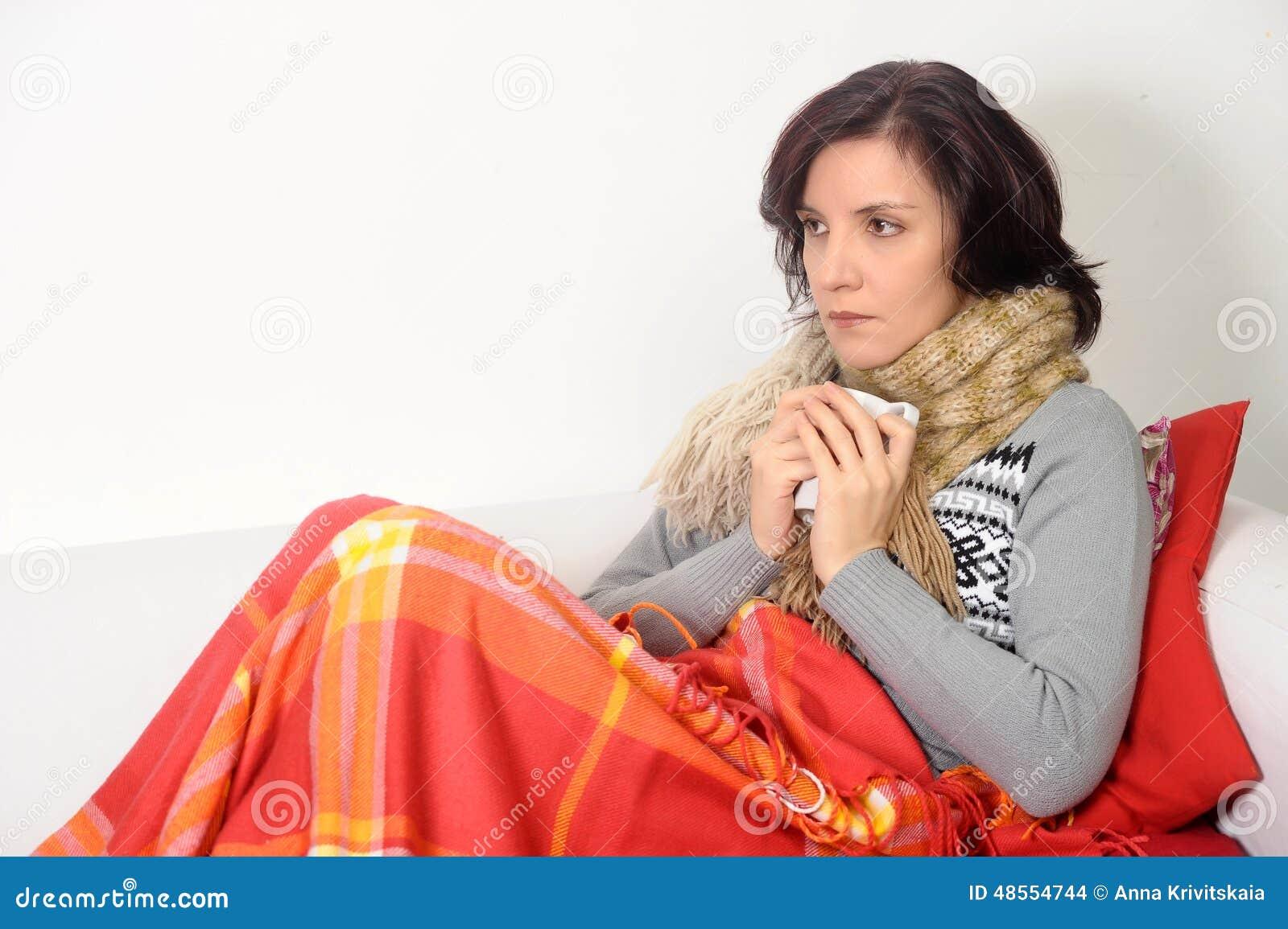 Mulher que come o chá bebendo da garganta inflamada fria