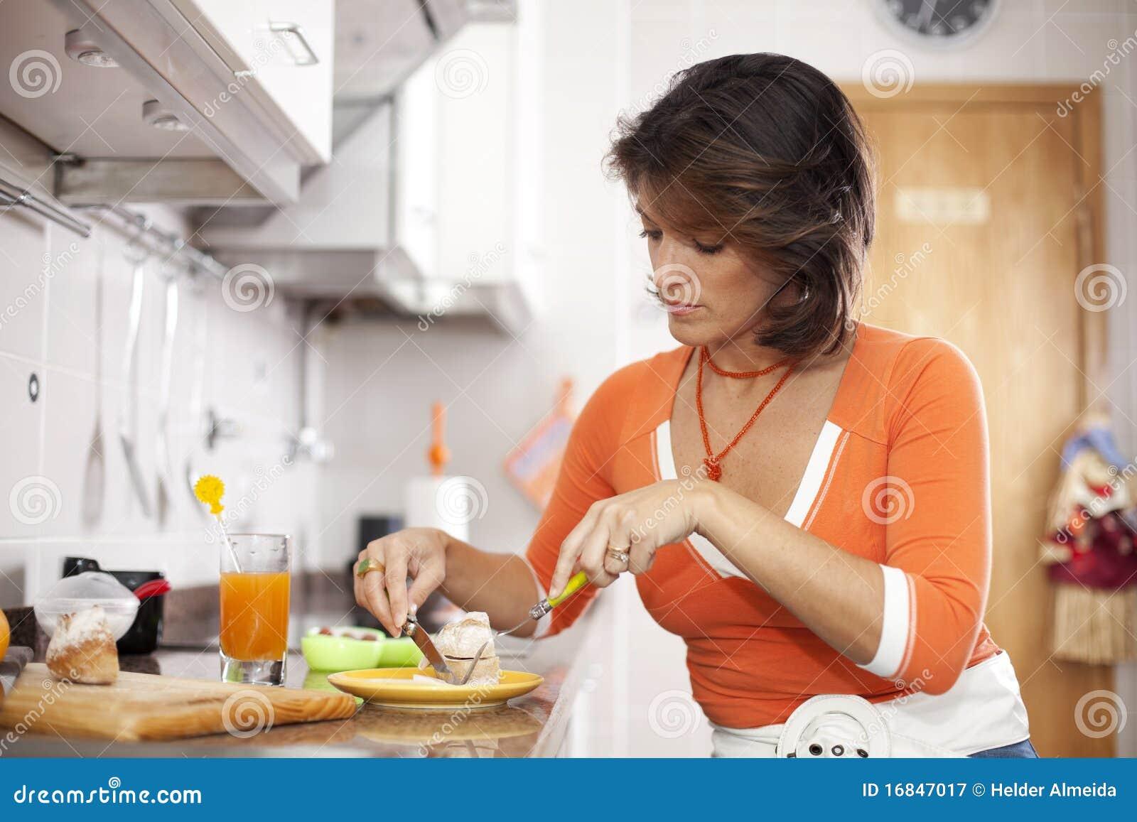 Mulher que come seu pequeno almoço