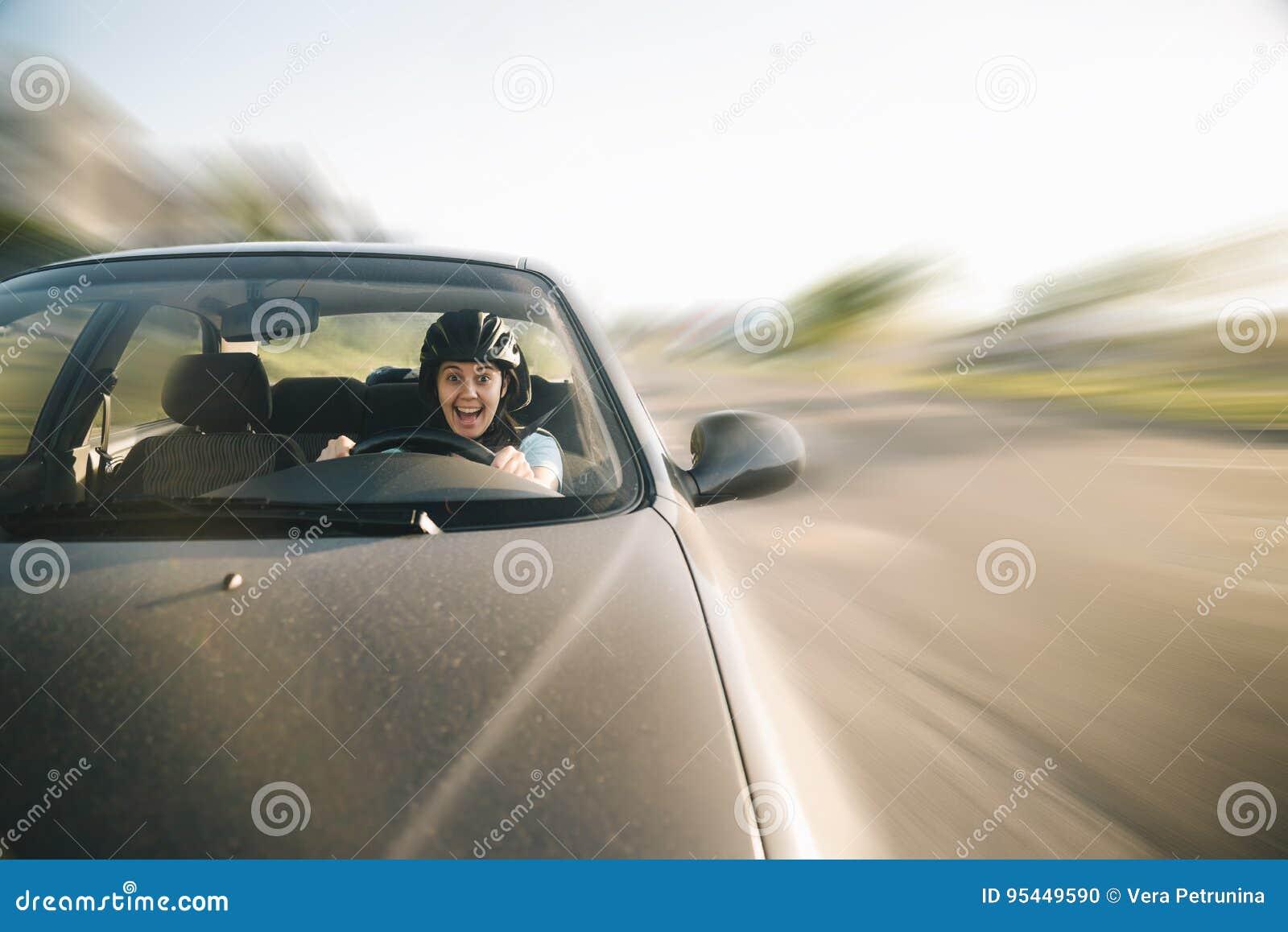 Mulher que conduz o carro no capacete com horror em sua cara