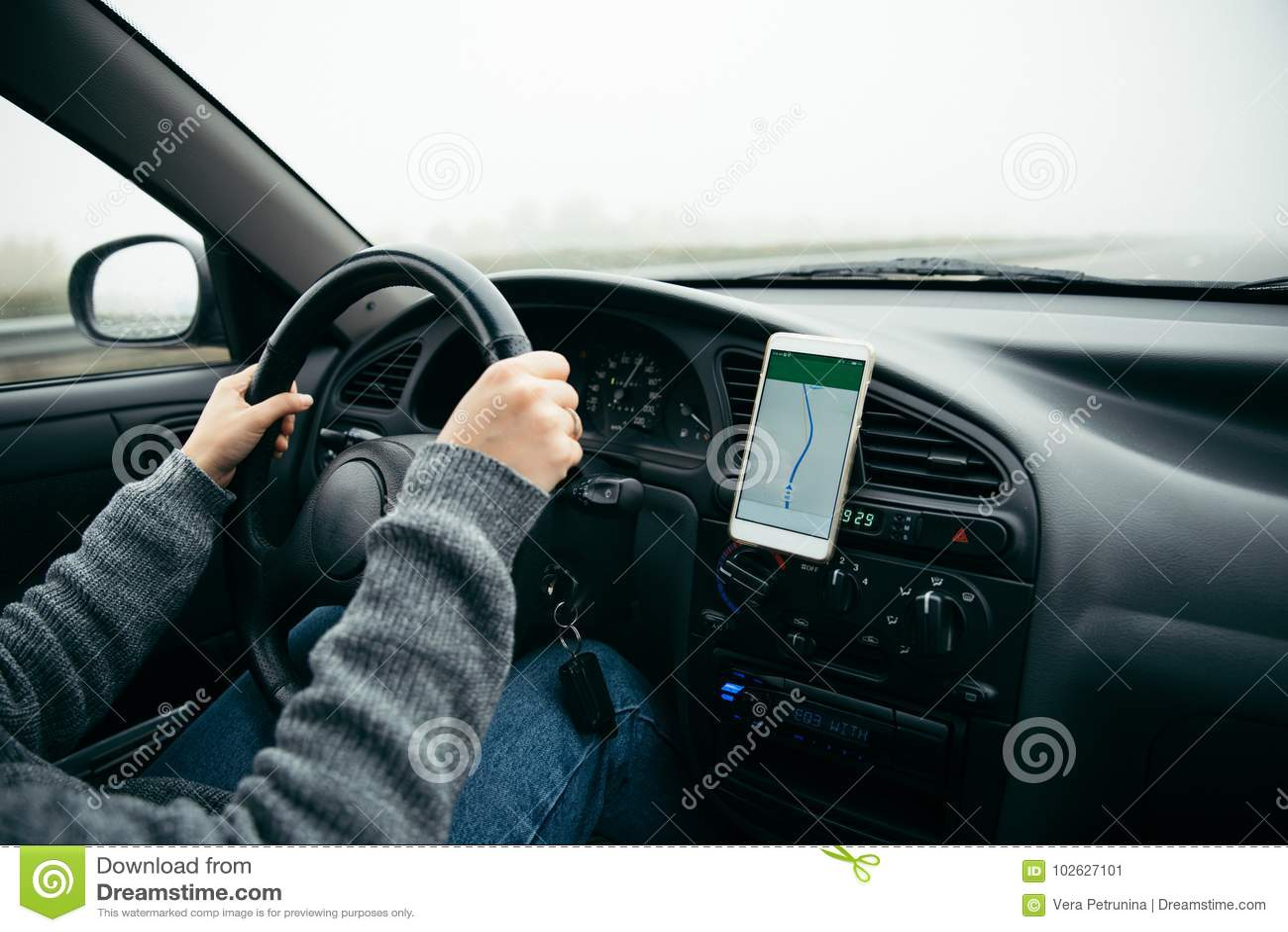 Mulher que conduz o carro pela estrada no tempo nevoento