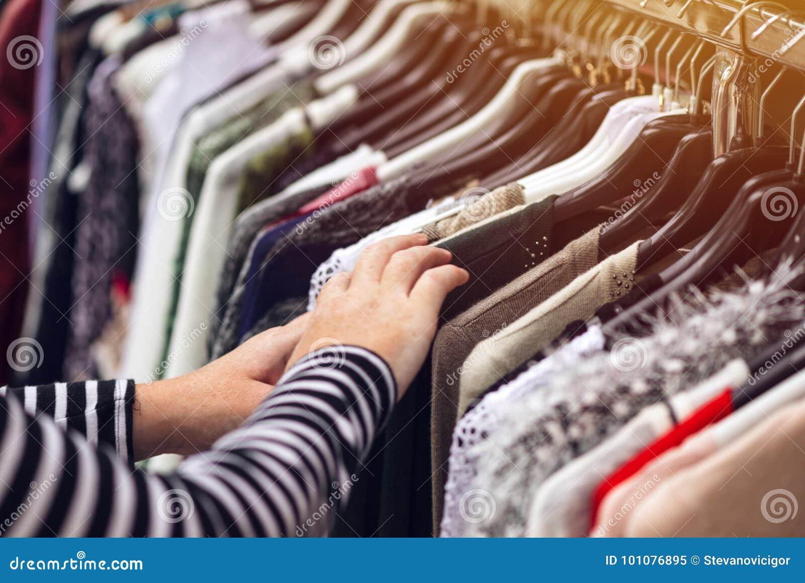 Mulher que consulta através da roupa no mercado de rua da segunda mão