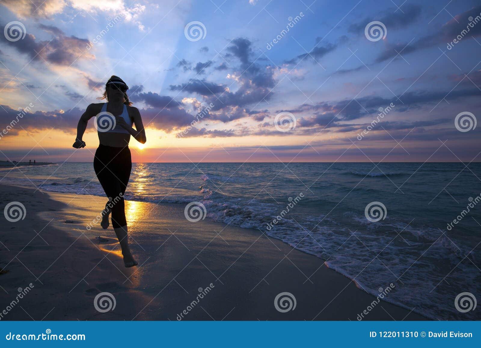 Mulher que corre na praia durante o por do sol