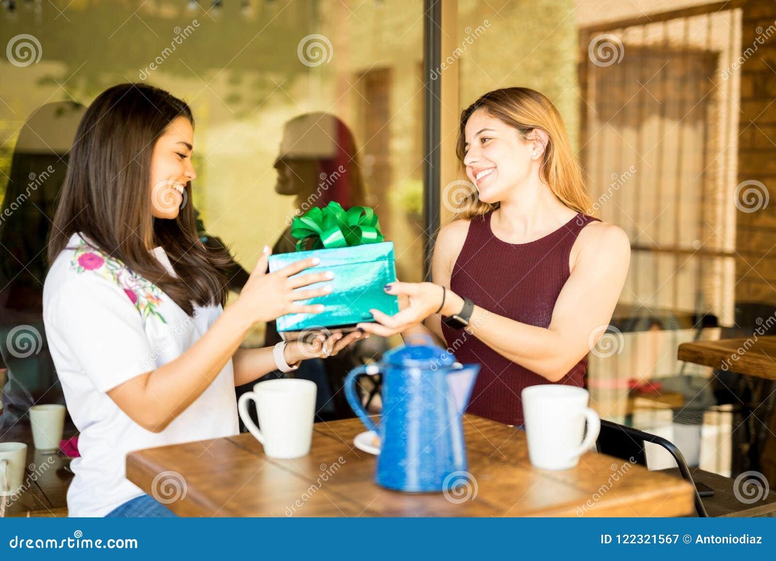 Mulher que dá um presente de aniversário ao amigo