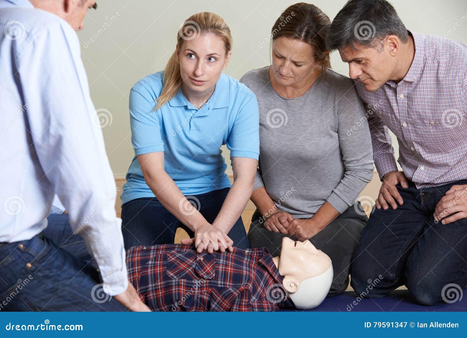 Mulher que demonstra o CPR no manequim do treinamento na classe dos primeiros socorros