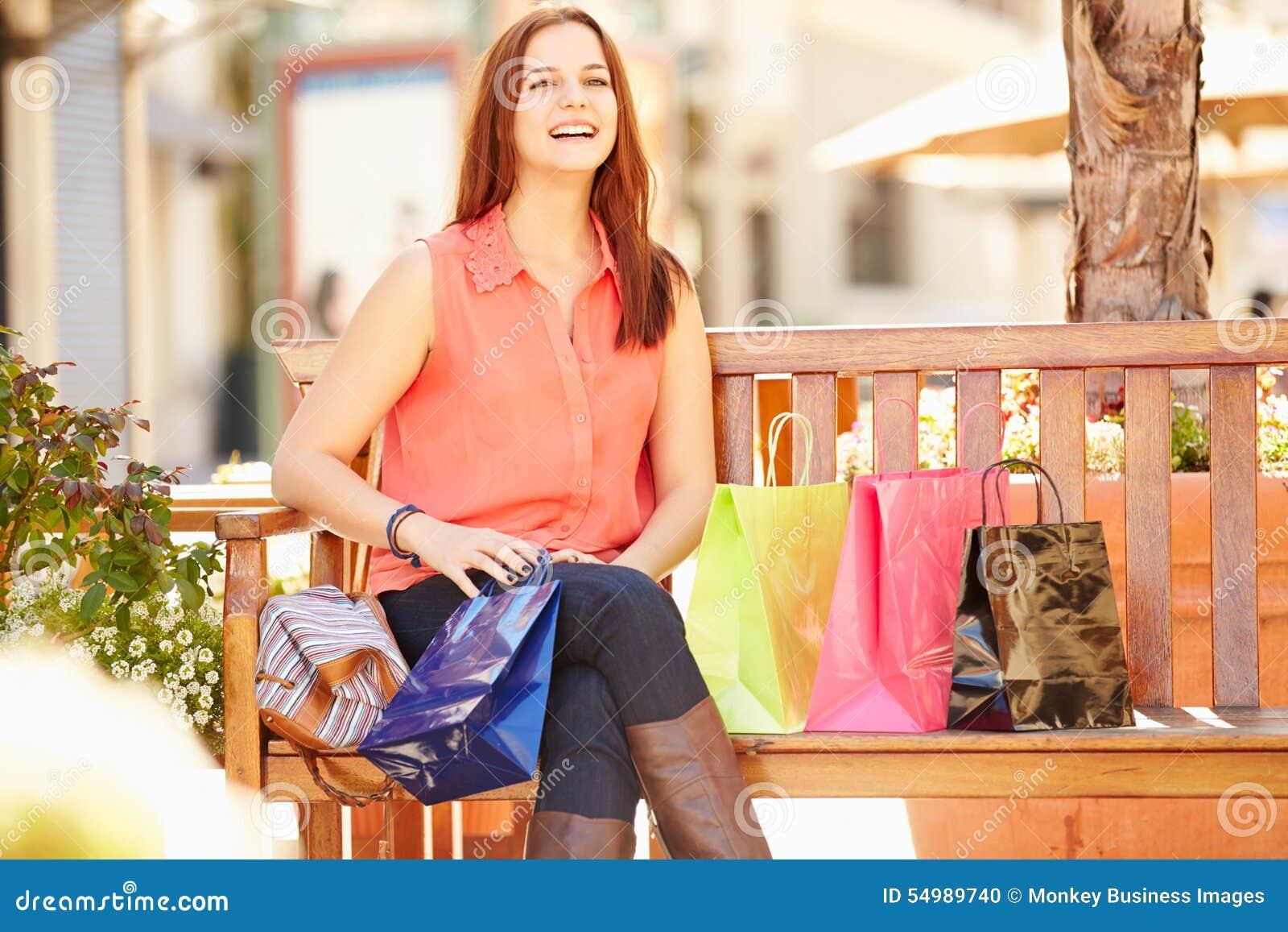 Mulher que descansa com os sacos de compras que sentam-se na alameda