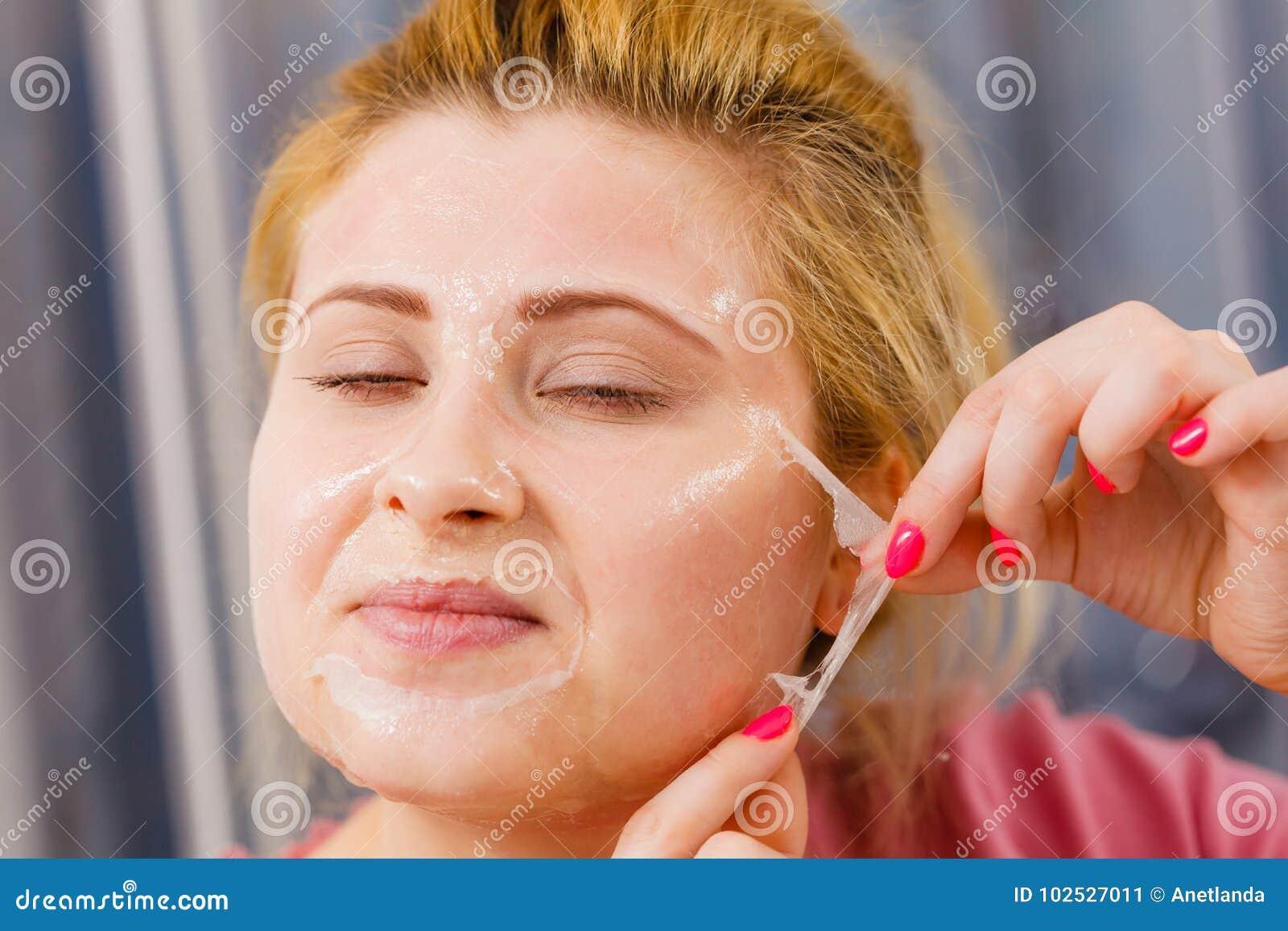 Mulher que descasca fora a máscara do gel da cara