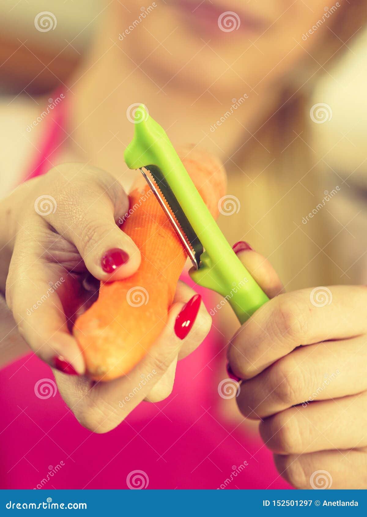 Mulher que descasca o vegetal da cenoura