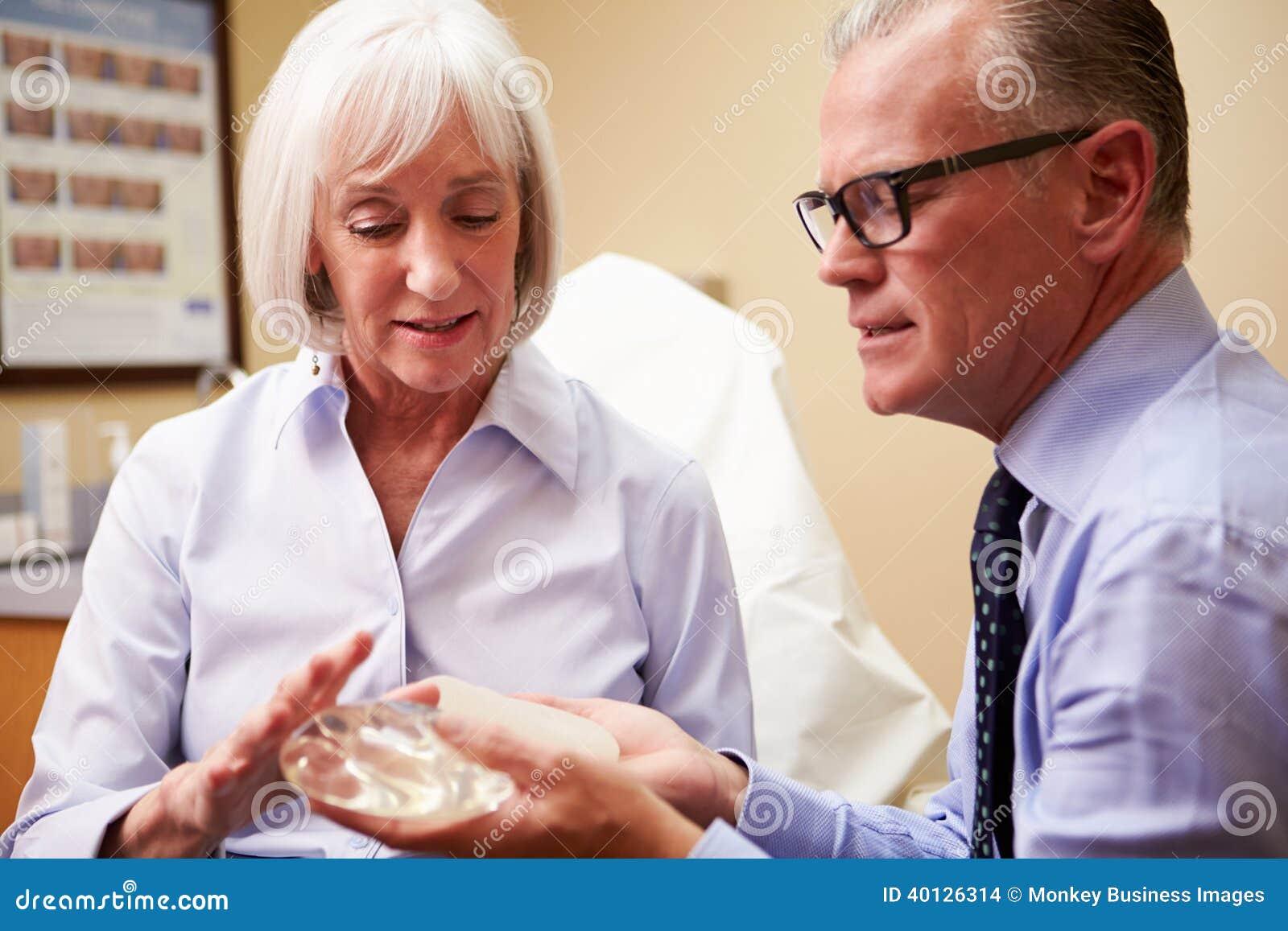 Mulher que discute o aumento do peito com o cirurgião plástico