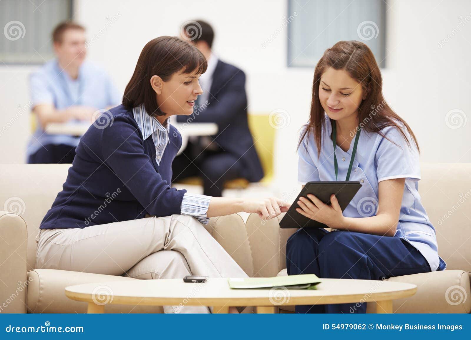 Mulher que discute resultados com a enfermeira On Digital Tablet