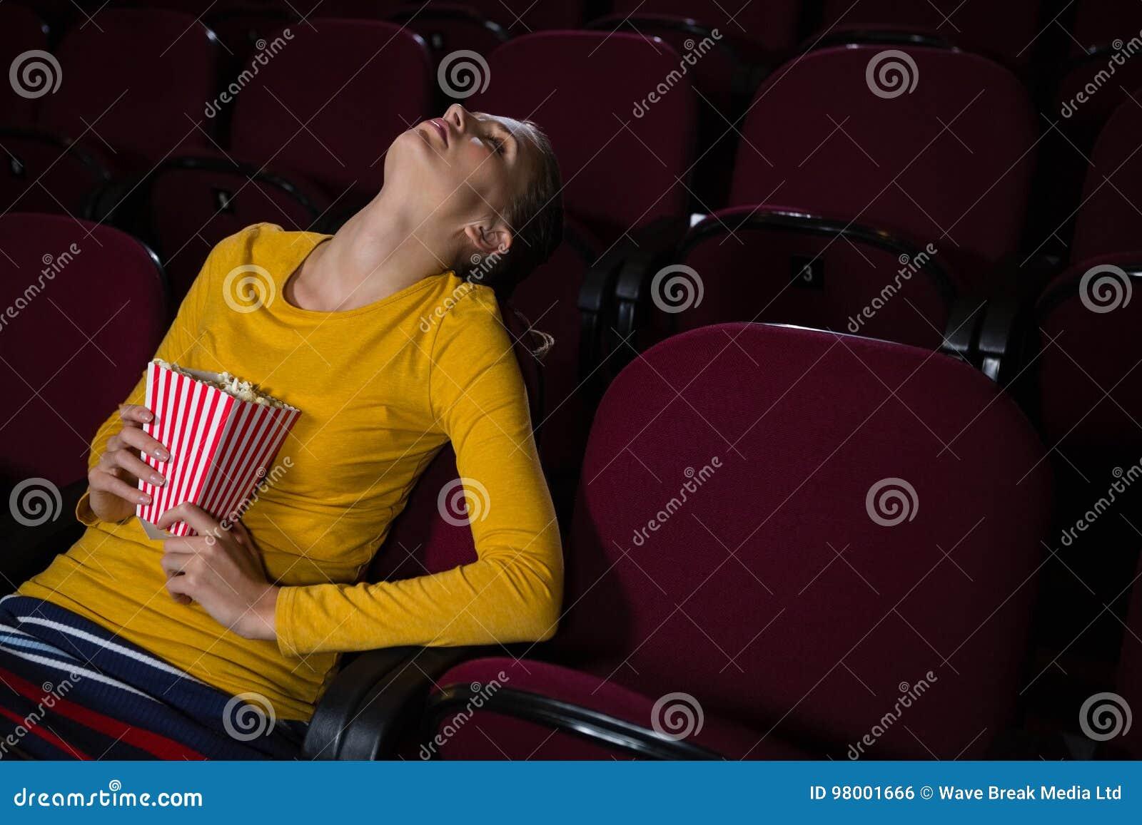 Mulher que dorme em um teatro de filme