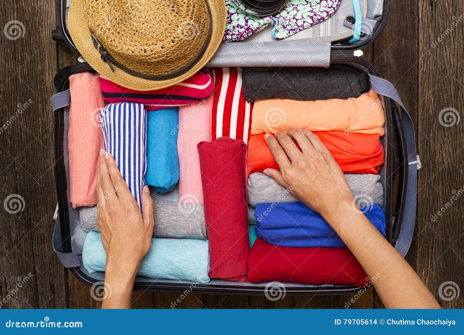 Mulher que embala uma bagagem para uma viagem nova