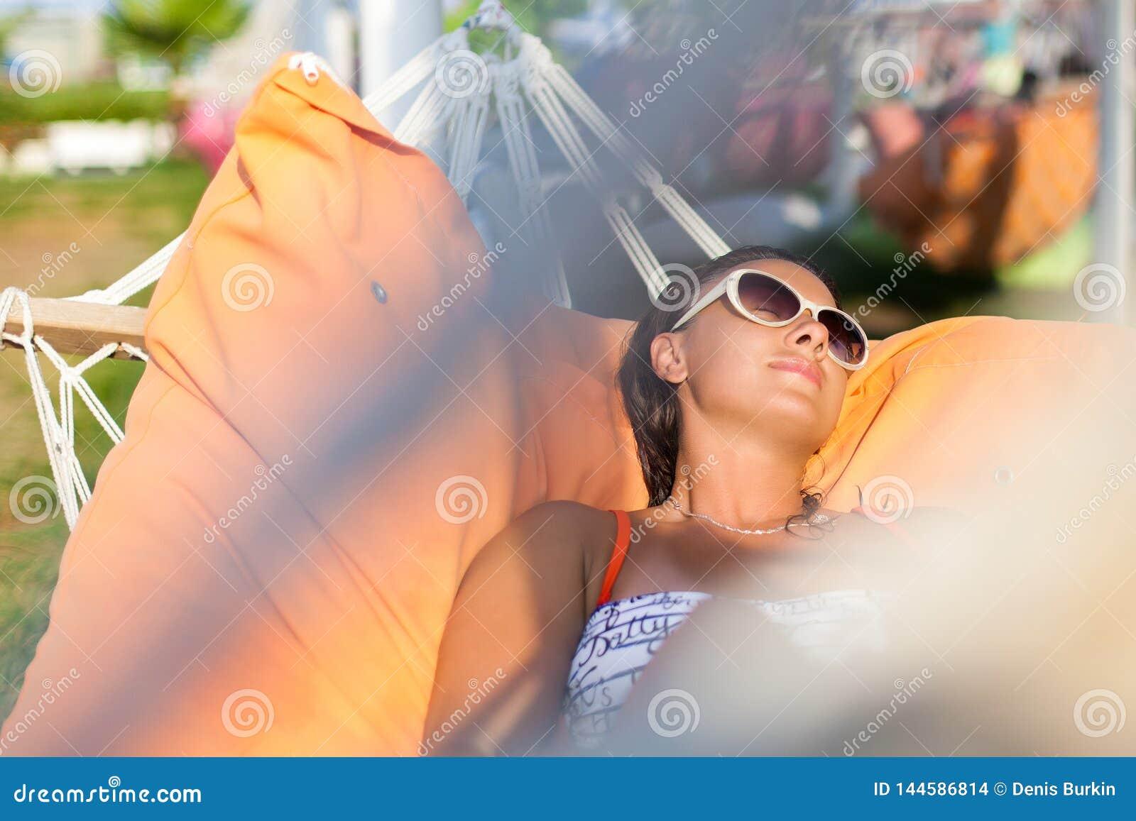 Mulher que encontra-se na rede Dia ensolarado quente Mulher que relaxa no hammock Close-up de uma mulher feliz nova que encontra-