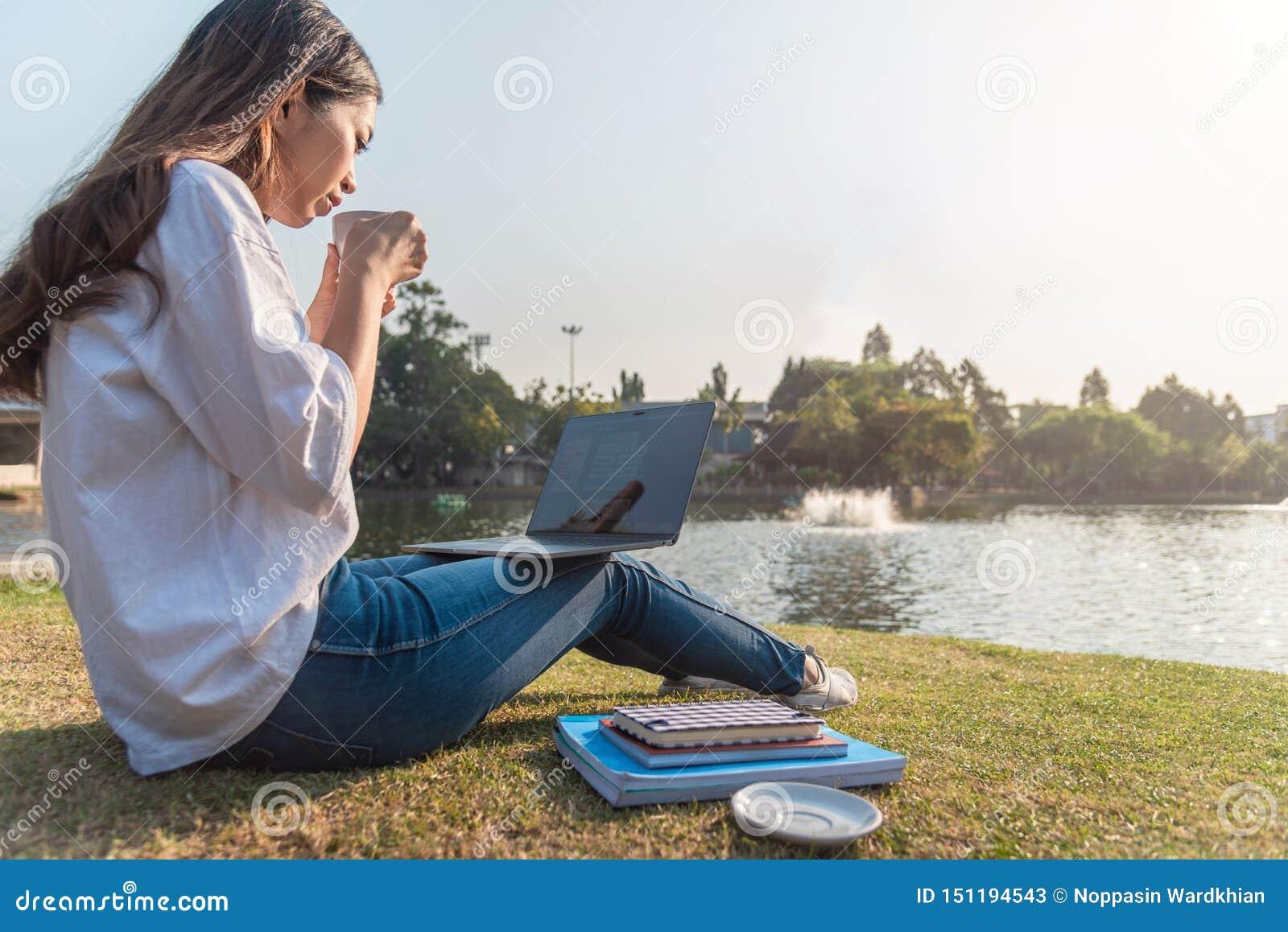 Mulher que encontra-se no fundamento na grama verde com a tabuleta durante o piquenique no parque