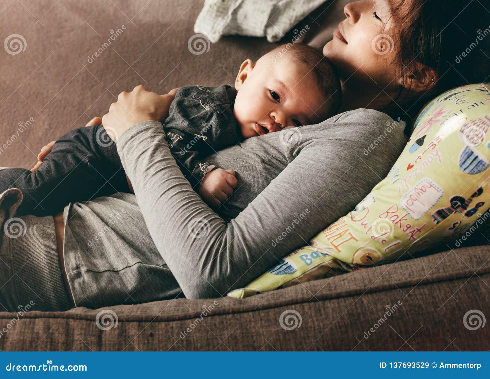 Mulher que encontra-se no sofá com os olhos fechados guardando seu bebê