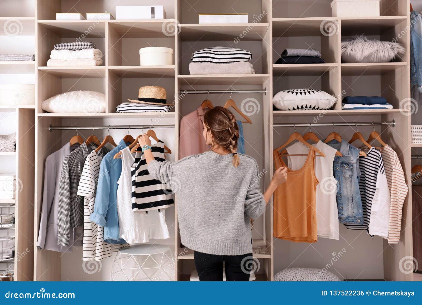 Mulher que escolhe o equipamento do grande armário do vestuário com roupa à moda