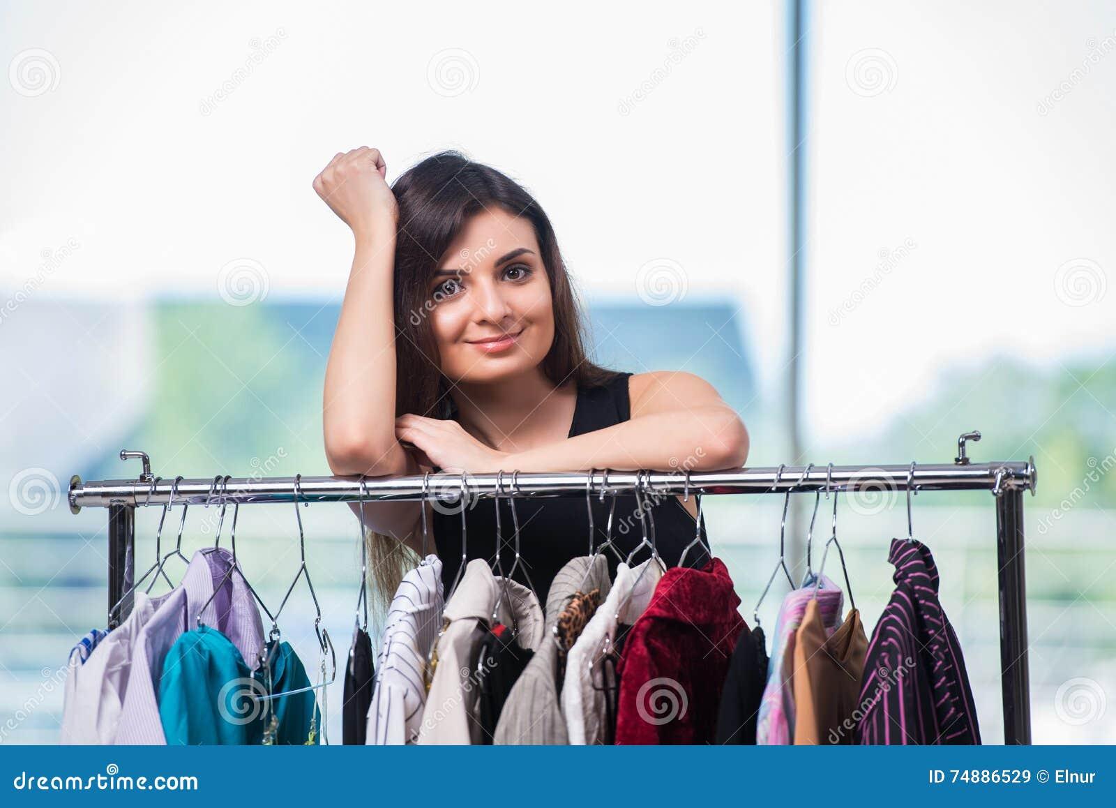 A mulher que escolhe a roupa na loja