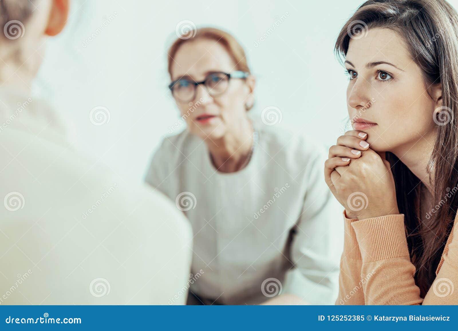 Mulher que escuta o terapeuta durante o treinamento a mulher de negócios no escritório