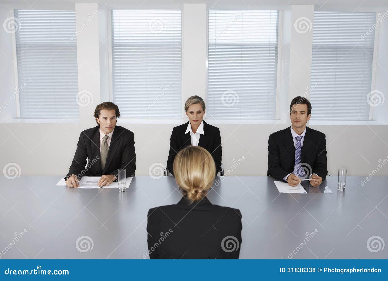 Mulher que está sendo entrevistada por executivos