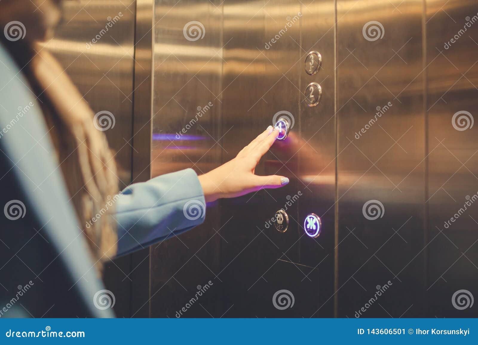 Mulher que est? no elevador e que pressiona o bot?o