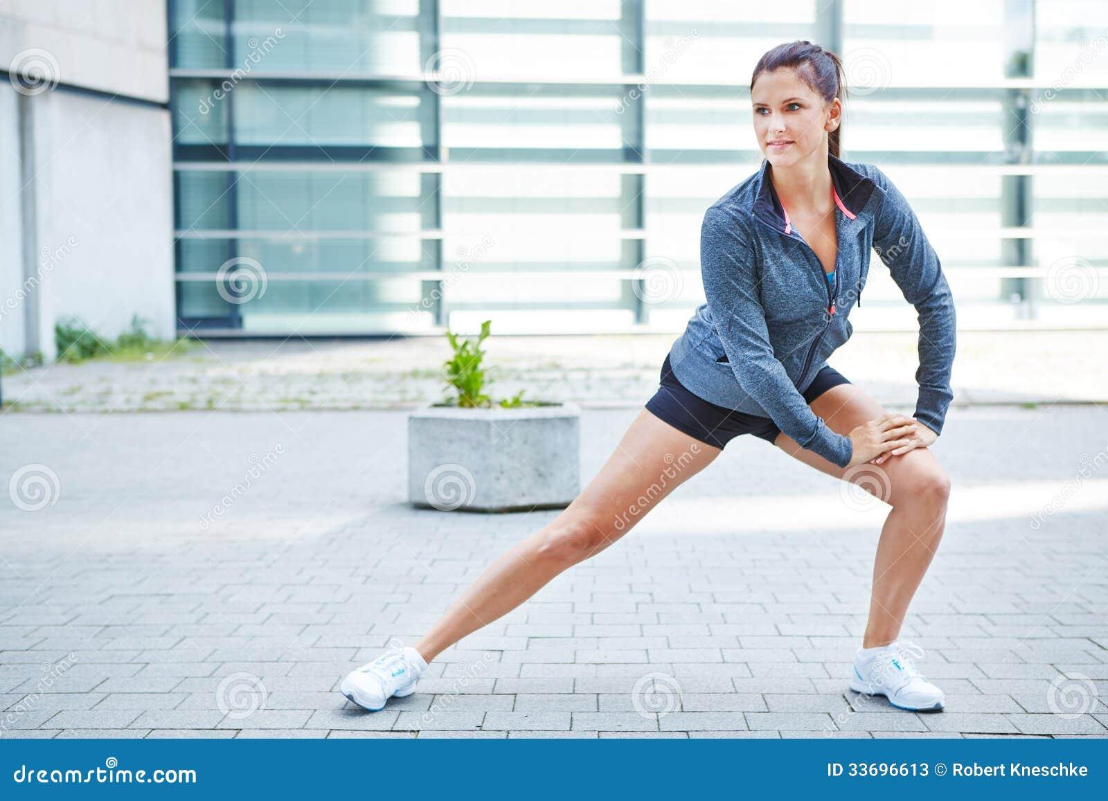 Mulher que estica antes de correr