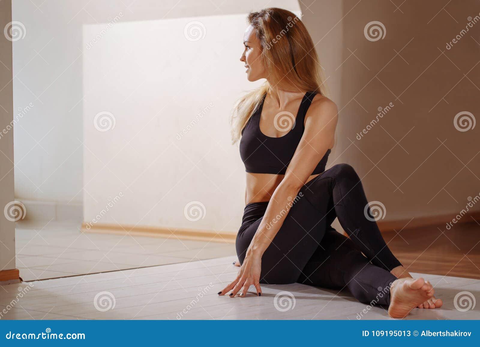 A mulher que estica a menina magro nova assentada da torção espinal faz o exercício