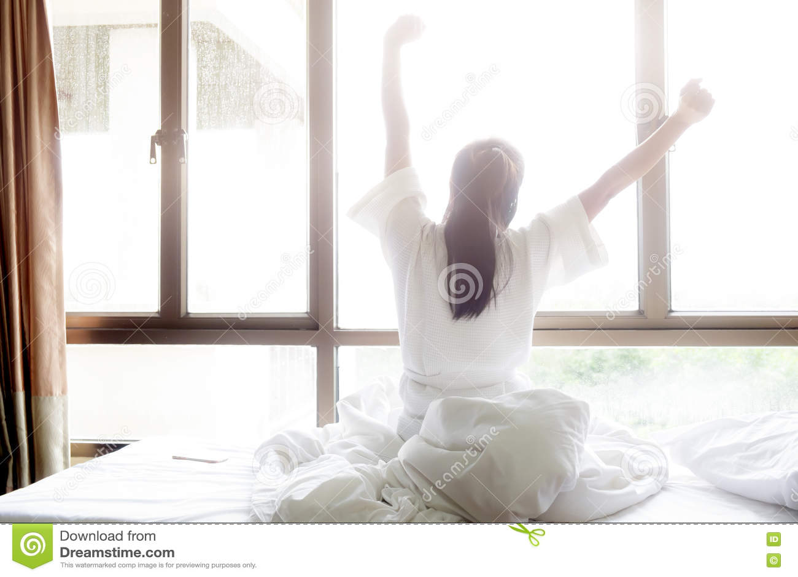 A mulher que estica na cama após acorda