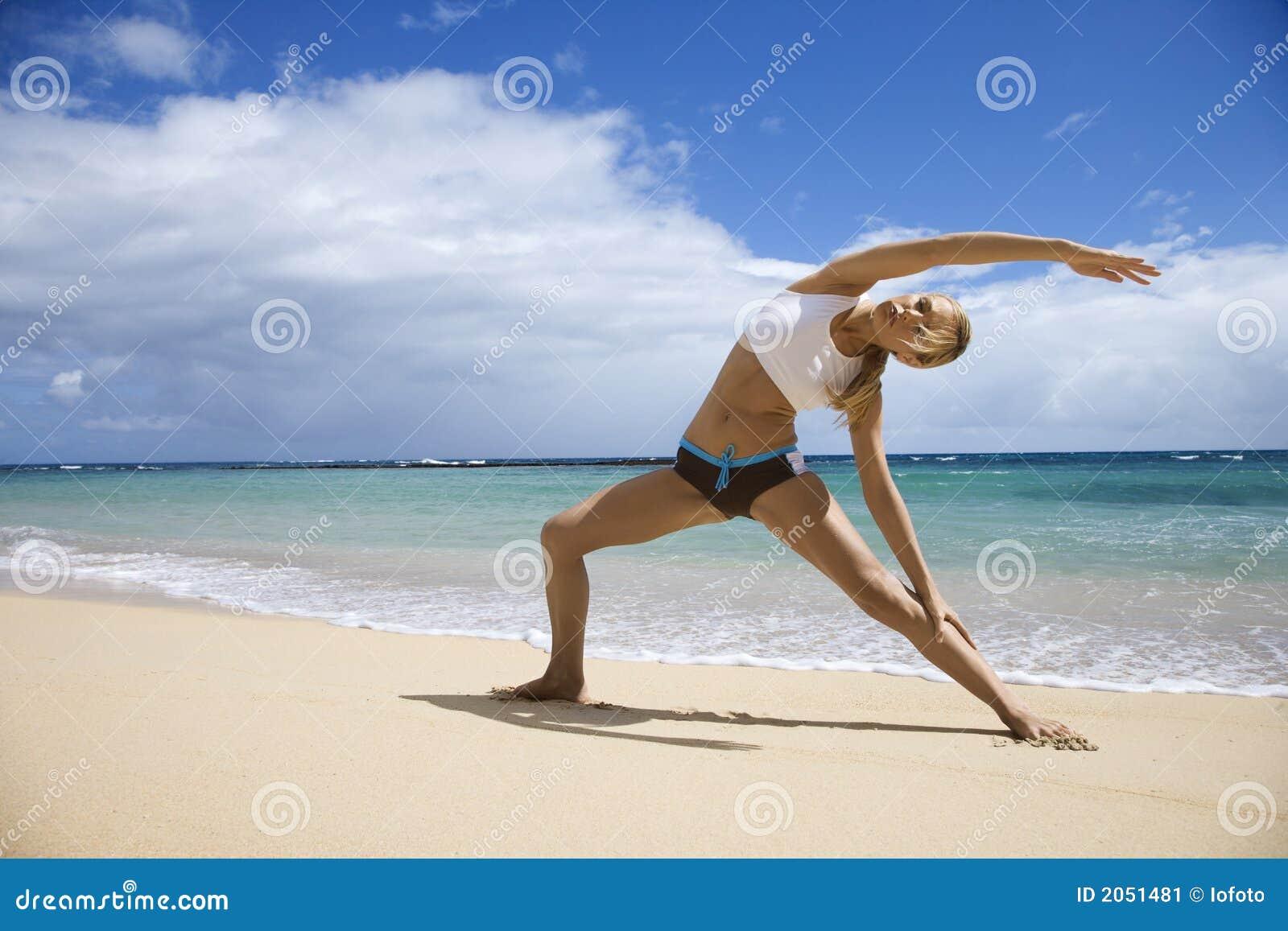 Mulher que estica na praia.