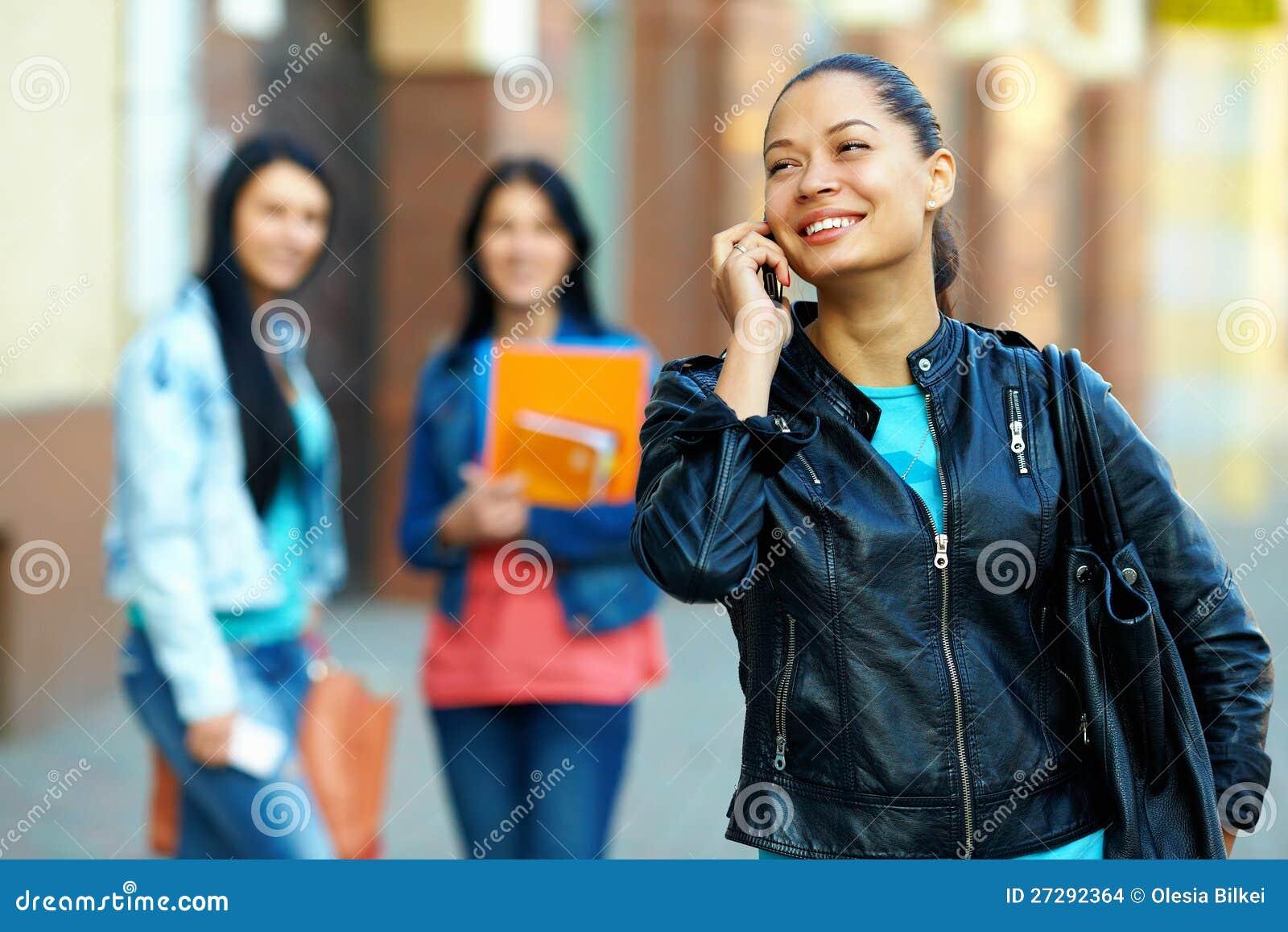 Mulher que fala no telefone móvel, na rua