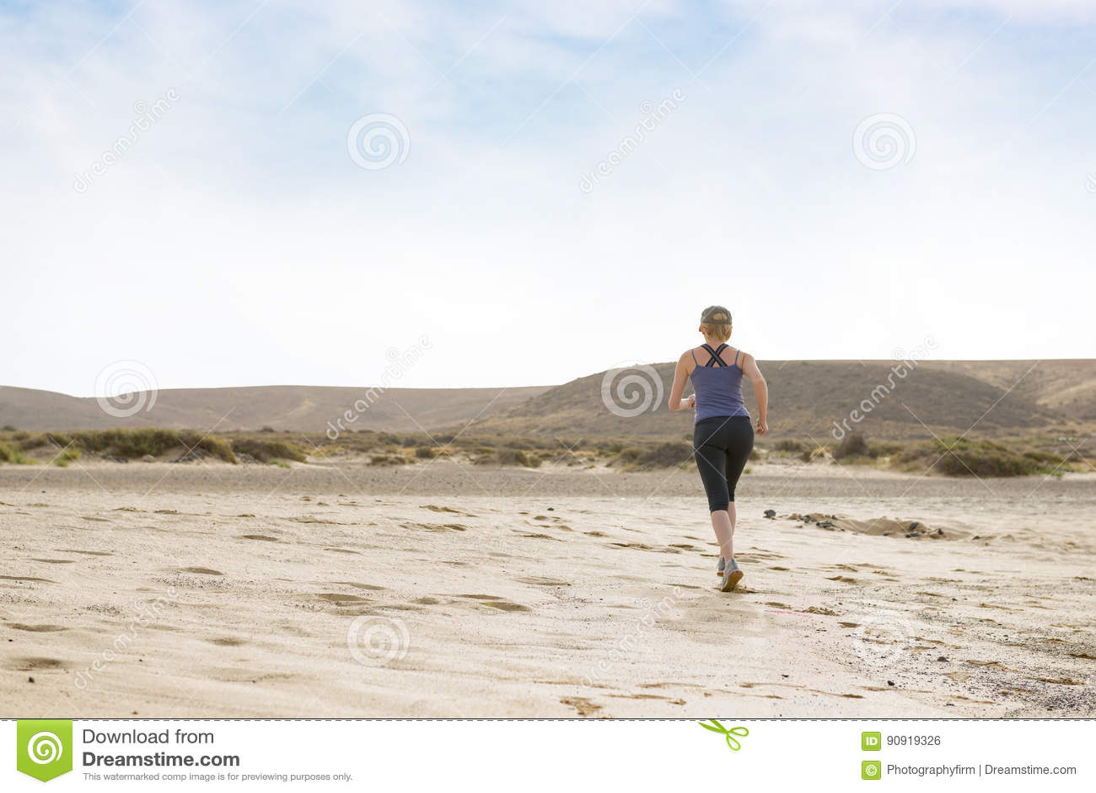 Mulher que faz a aptidão da manhã corrida no deserto